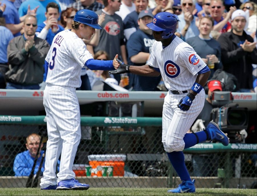Alfonso Soriano, right, celebrates with third base coach David Bell after hitting a two-run home run during the third inning of a baseball game against the Cincinnati Reds in Chicago, Saturday, May 4, 2013.