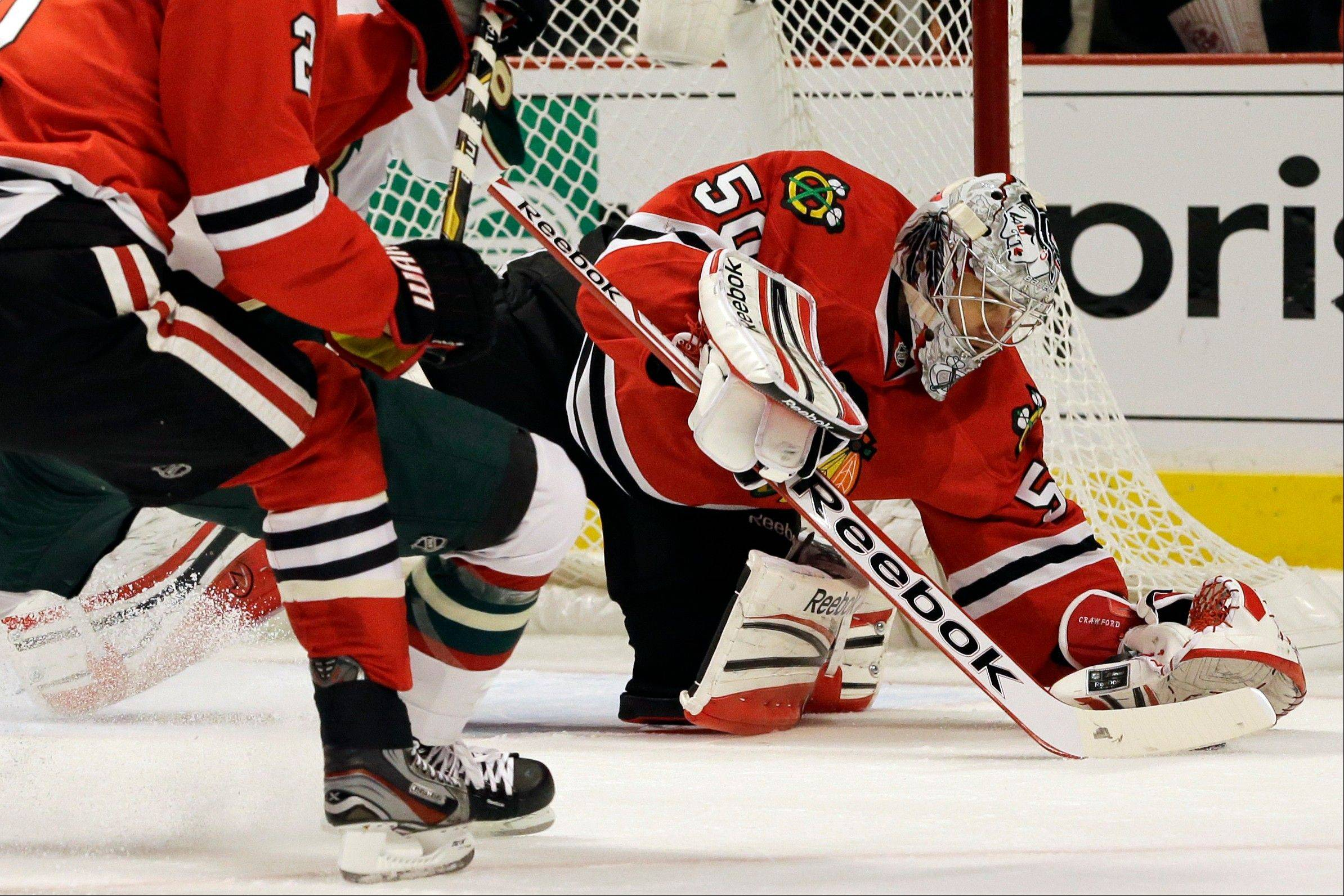 Chicago Blackhawks goalie Corey Crawford, right, saves a shot by Minnesota Wild's Charlie Coyle (not shown) during the first period of Game 2 of an NHL hockey Stanley Cup first-round playoff series in Chicago, Friday, May 3, 2013.