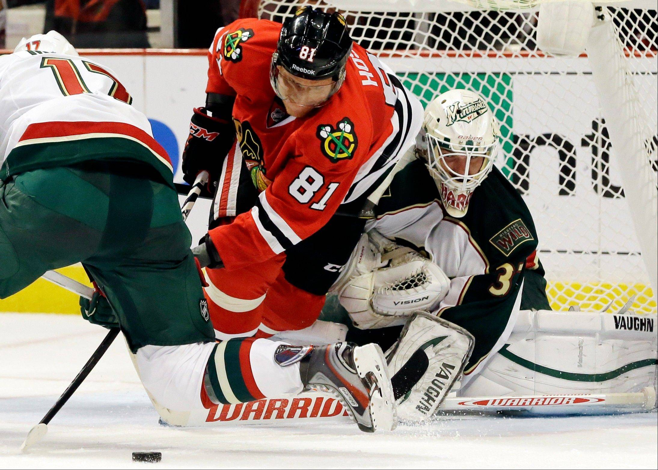 Chicago Blackhawks' Marian Hossa (81) controls the puck against Minnesota Wild goalie Josh Harding (37) during the second period of Game 2 of an NHL hockey Stanley Cup first-round playoff series in Chicago, Friday, May 3, 2013.