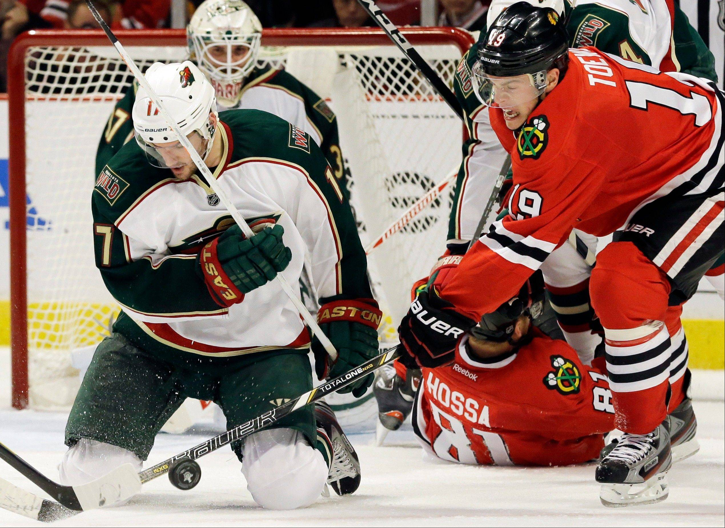 Chicago Blackhawks' Jonathan Toews (19) battles for the puck against Minnesota Wild's Torrey Mitchell (17) during the second period of Game 2 of an NHL hockey Stanley Cup first-round playoff series in Chicago, Friday, May 3, 2013.