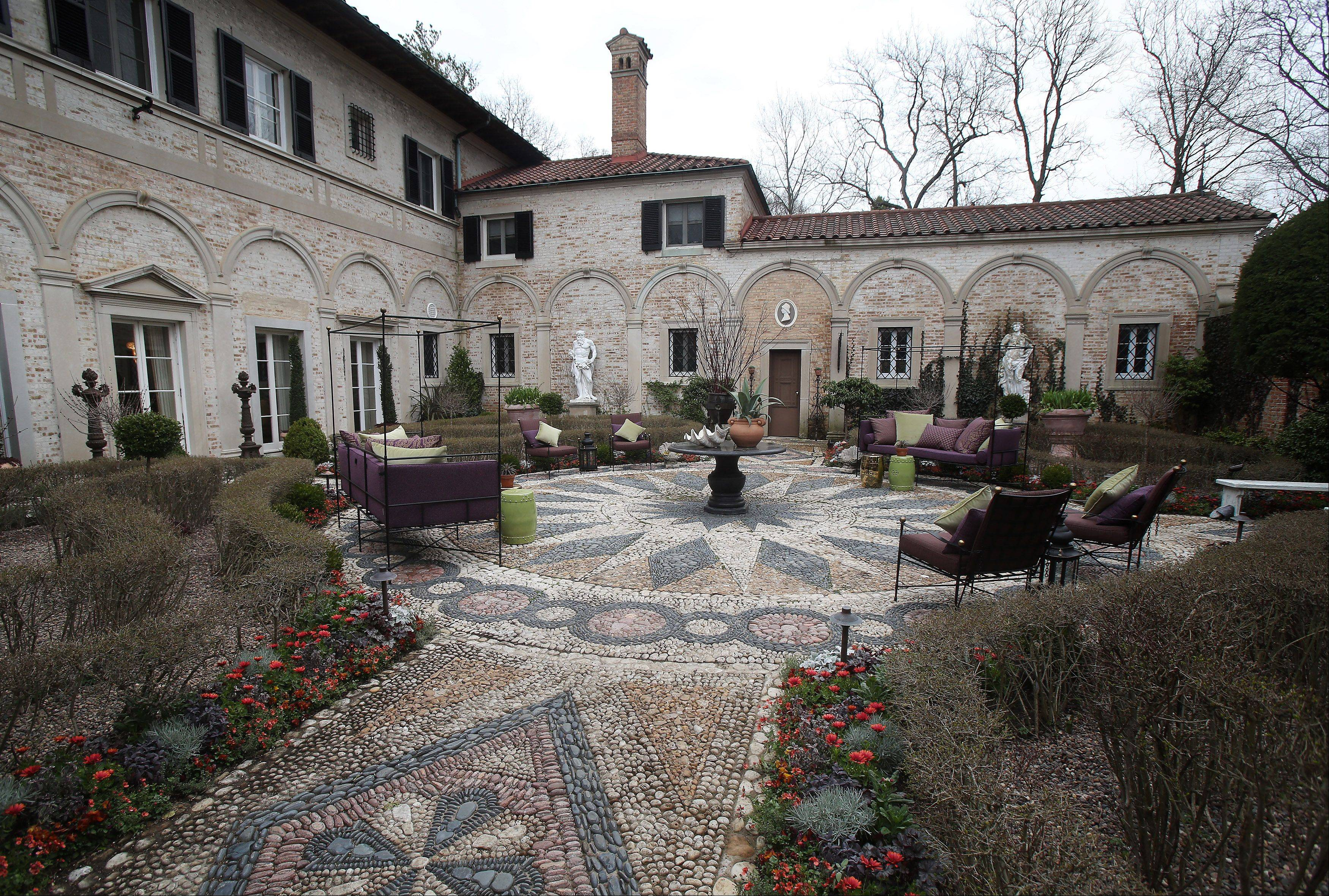 In the courtyard of the Lake Forest Showhouse, Craig Bergman Landscape Design complements architect David Adler's pathway created with rocks from the beaches of Lake Michigan.