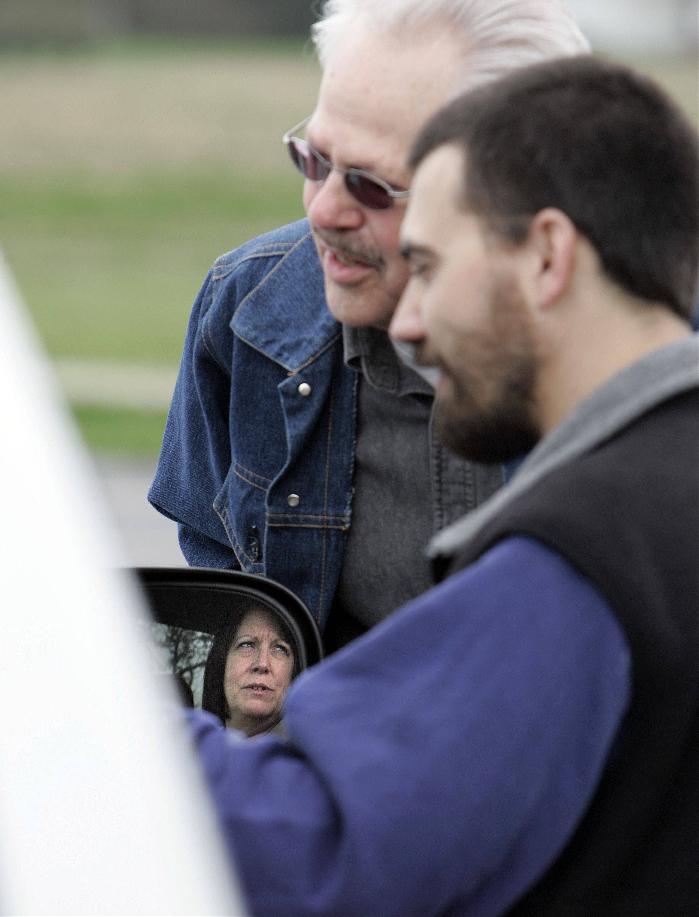 "Reflected in her car mirror, Karin Shiderler of Wonder Lake prays with Don Gorder, of Huntley, center, and organizer George Delask, of Country Evangelical Covenant Church In Dekalb. The ""Drive-Thru Prayer"" service was in the church parking lot at the corner of McDonald Road and Route 47 in Campton Hills, Thursday."
