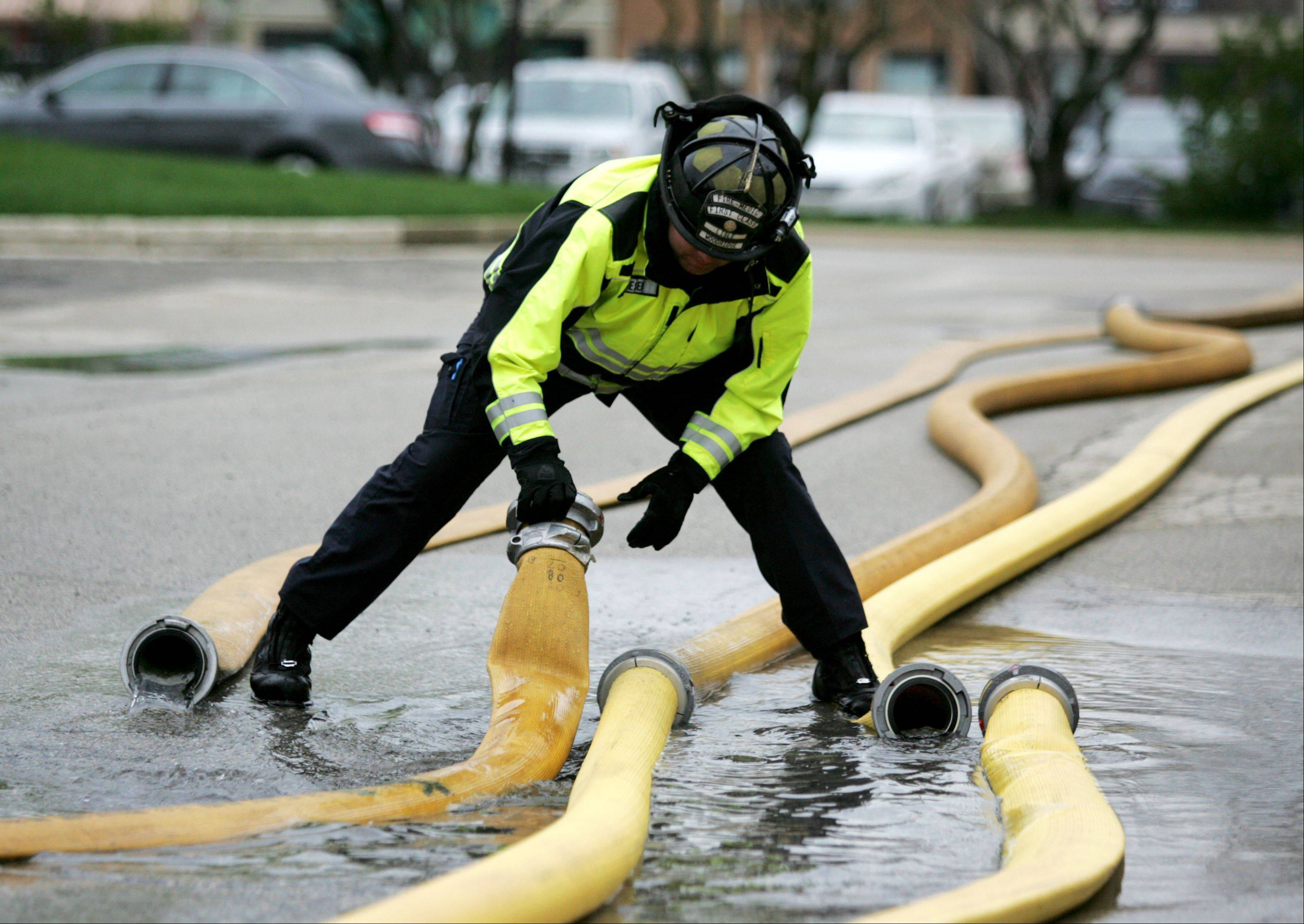 Lisle Woodridge Firefighter Austin Gieser decouples hoses after checking pressure in five-inch supply lines, looking for possible defects. The annual test is mandated by the National Fire Protection Agency.