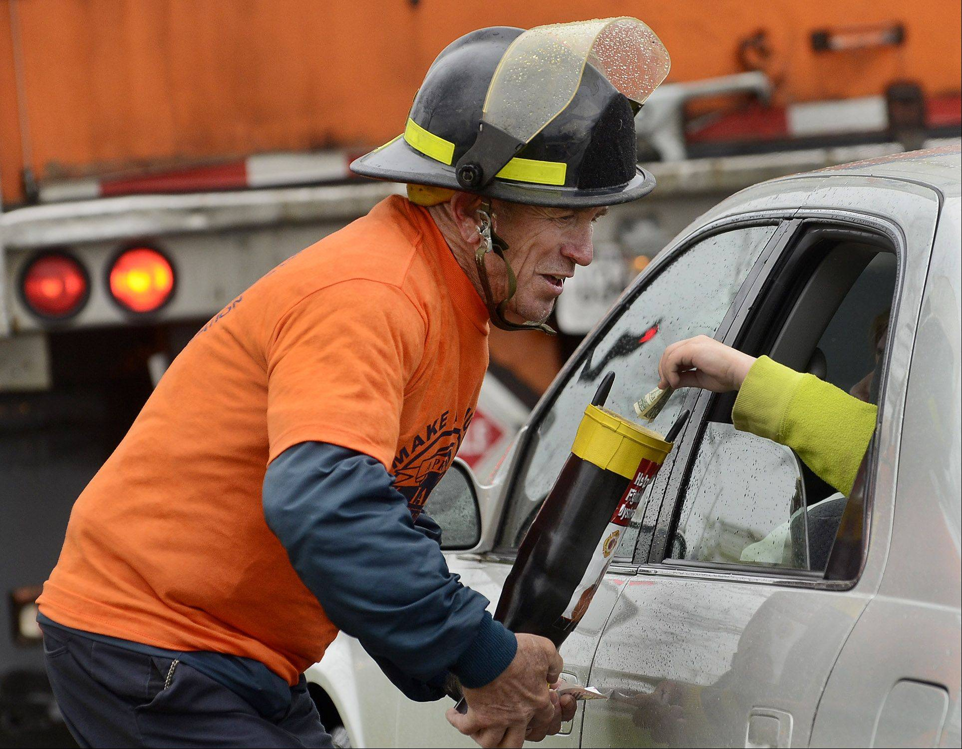 Fighfighter Bill Ahlman gets a contribution from a motorist on the corner of Palatine and Arlington Heights Roads during the Arlington Heights Fire Department and the Muscular Dystrophy Association annual Boot Drive.
