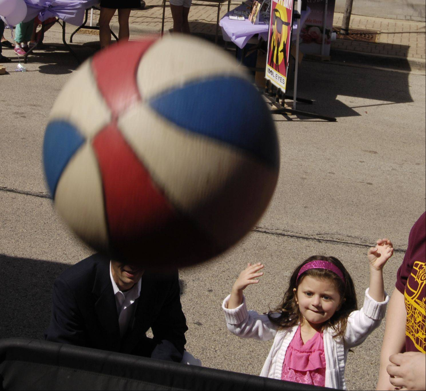Lilly Sunny, 4, of Lombard, tries to sink a basketball during the Lilac Time Art and Craft Fair in Lombard Sunday.