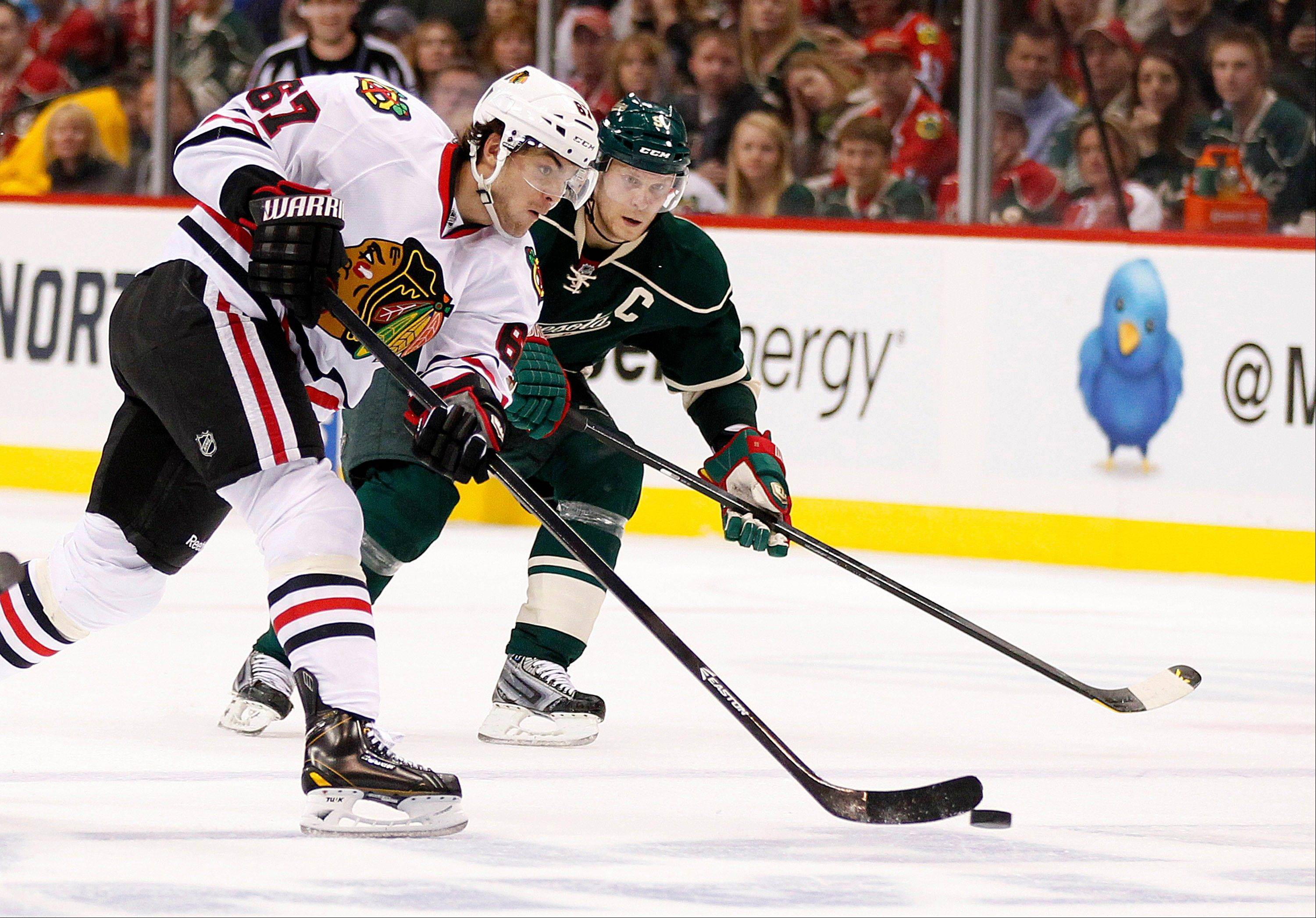 Chicago Blackhawks' Michael Frolik (shoots against Minnesota Wild's Mikko Koivu in the second period of Game 3 of an NHL hockey Stanley Cup playoff series Sunday, May 5, 2013 in St. Paul, Minn.