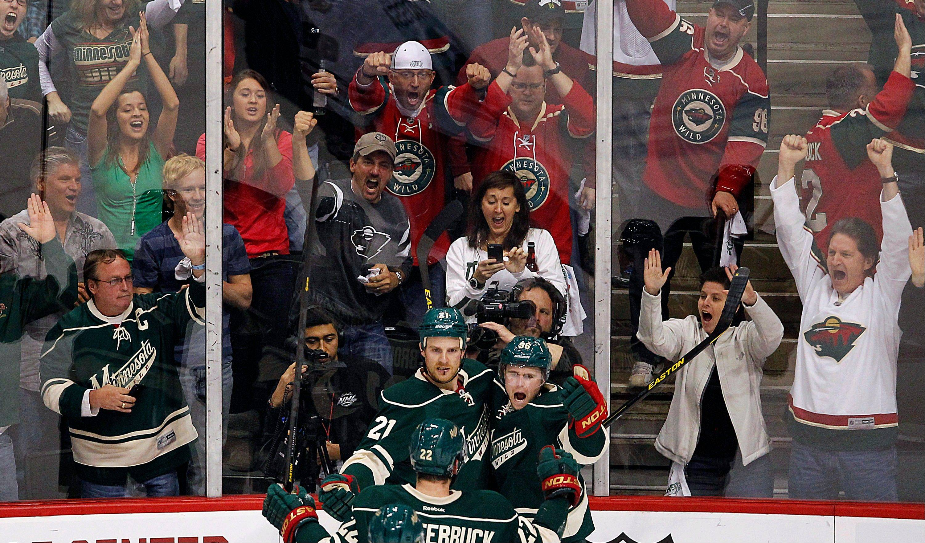 Minnesota Wild's Pierre-Marc Bouchard and Kyle Brodziak celebrate Bouchard's goal against the Chicago Blackhawks in the first period. The Wild defeated the Blackhawks 3-2 in overtime.
