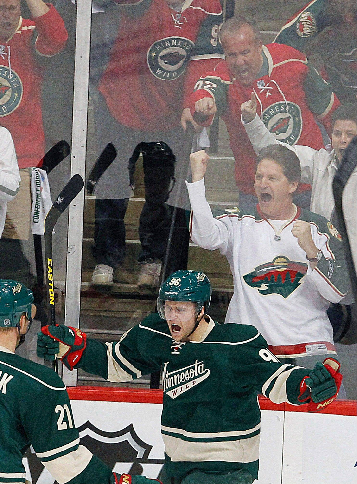 As fans, background, react, Minnesota Wild's Pierre-Marc Bouchard celebrates his goal against the Chicago Blackhawks in first period.