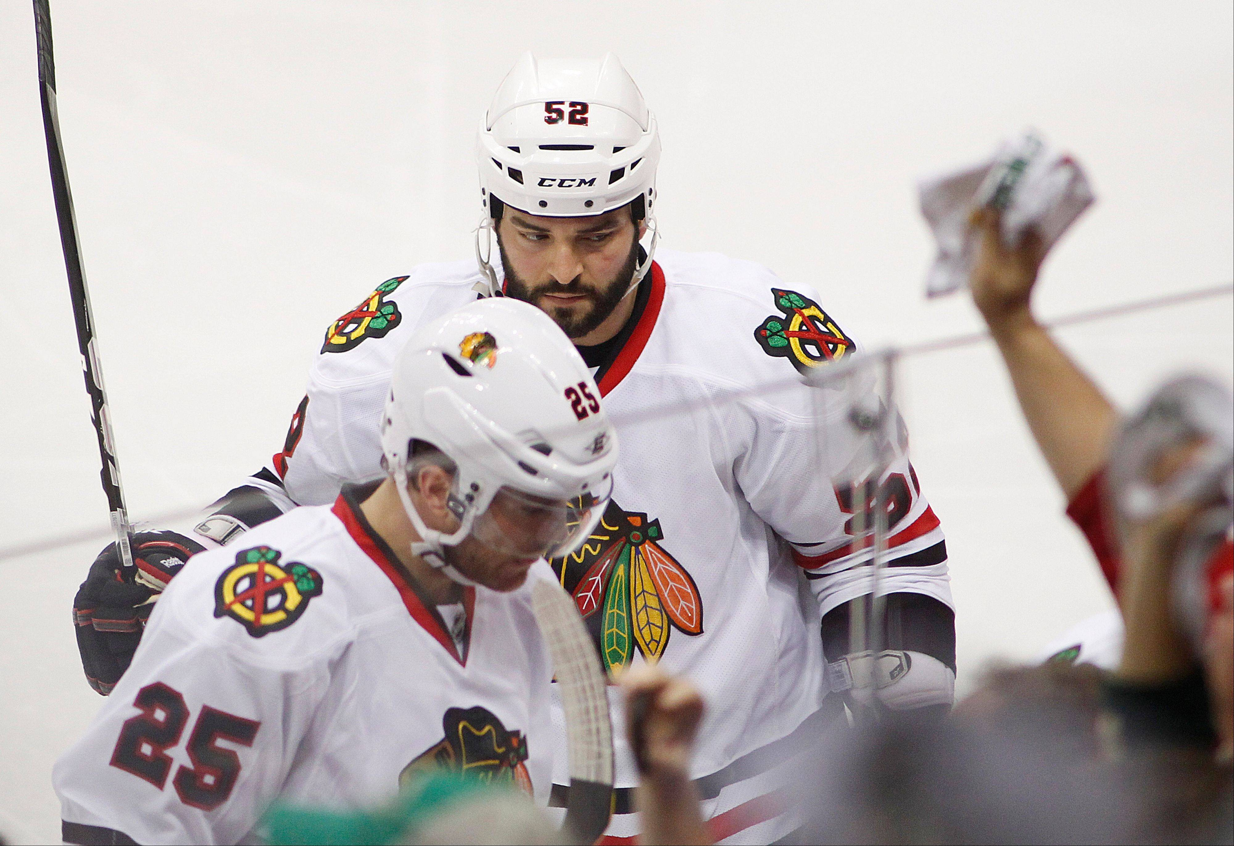 Chicago Blackhawks players Brandon Bollig, top, and Viktor Stalberg leave the ice after Minnesota Wild's Jason Zucker scored a goal in the overtime period. The Wild defeated the Blackhawks 3-2.