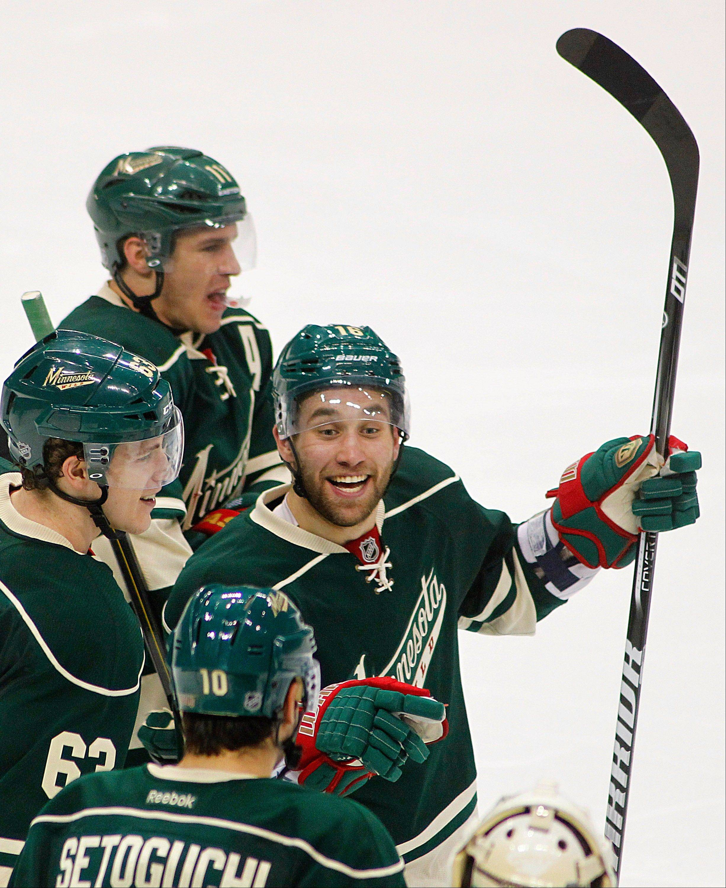 Minnesota Wild's Jason Zucker celebrates his overtime goal against the Chicago Blackhawks with teammates Zach Parise, top, Charlie Coyle and Devin Setoguchi during Game 3. The Wild defeated the Blackhawks 3-2.
