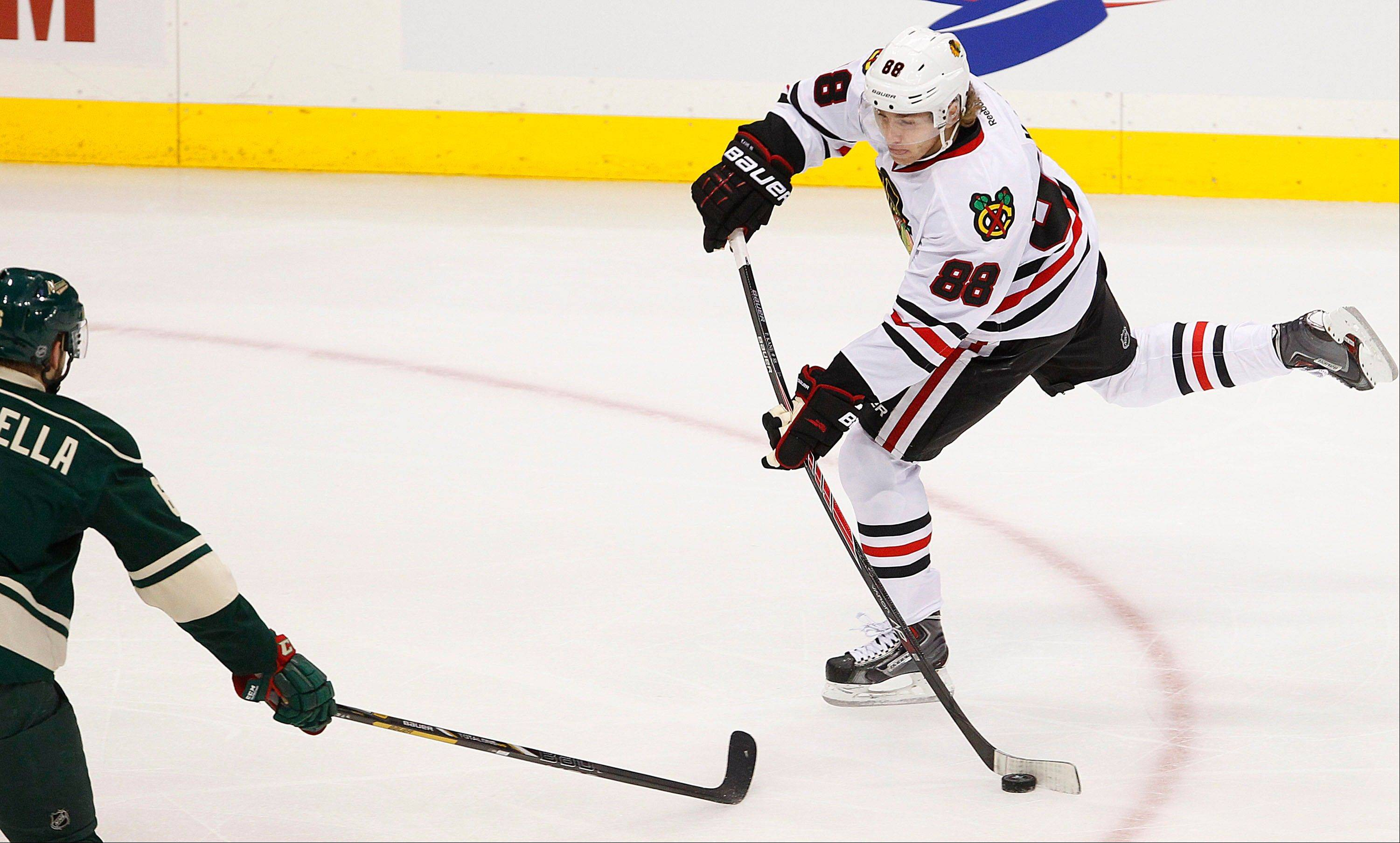Chicago Blackhawks' Patrick Kane shoots in front of Minnesota Wild's Ryan Sutter in the first period. Minnesota won 3-2 in overtime.