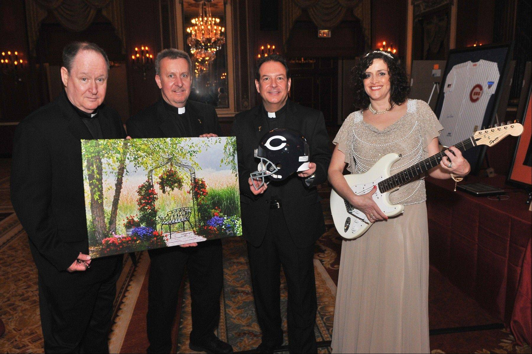 Pictured from left to right, Alexian Brothers Daniel McCormick (Provincial), Brother Paul Magner and Brother Tom Klein with Melanie Furlan, Vice President, Advancement, for Alexian Brothers Foundation, show off the silent auction items, including an autographed guitar by John Rzeznik of the Goo Goo Dolls.