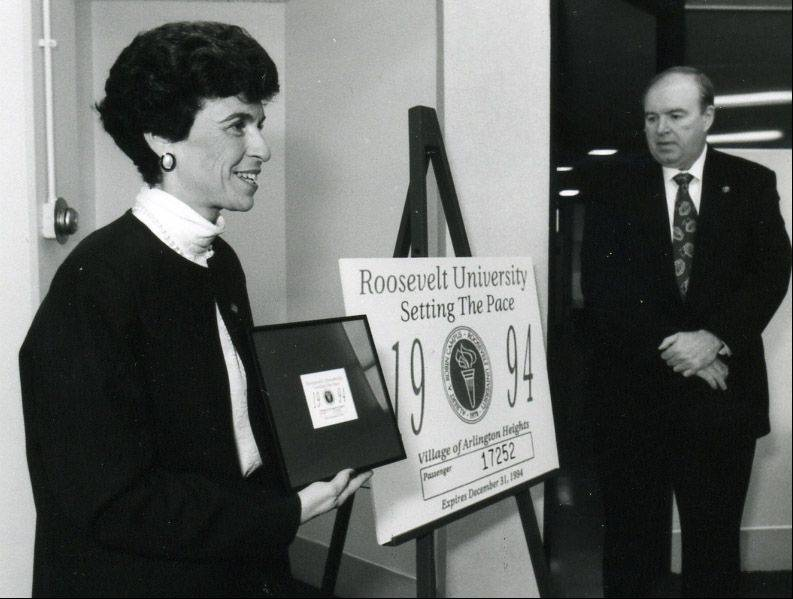 Arlene Mulder presents Frank Cassell, Roosevelt University dean, with the 1993 Arlington Heights vehicle sticker honoring the university. From 1987 to 1996, Roosevelt's northwest suburban campus was in the former Forest View High School, 2121 S. Goebbert Road, Arlington Heights.