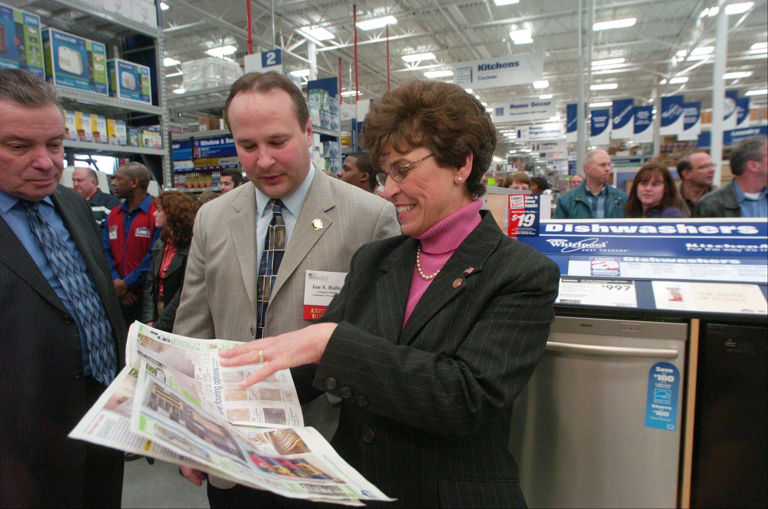 The mayor and Jon Ridler, executive director of the Chamber of Commerce, flip through a sales pamphlet at the opening of the Arlington Heights Lowe's on Jan. 11, 2006.
