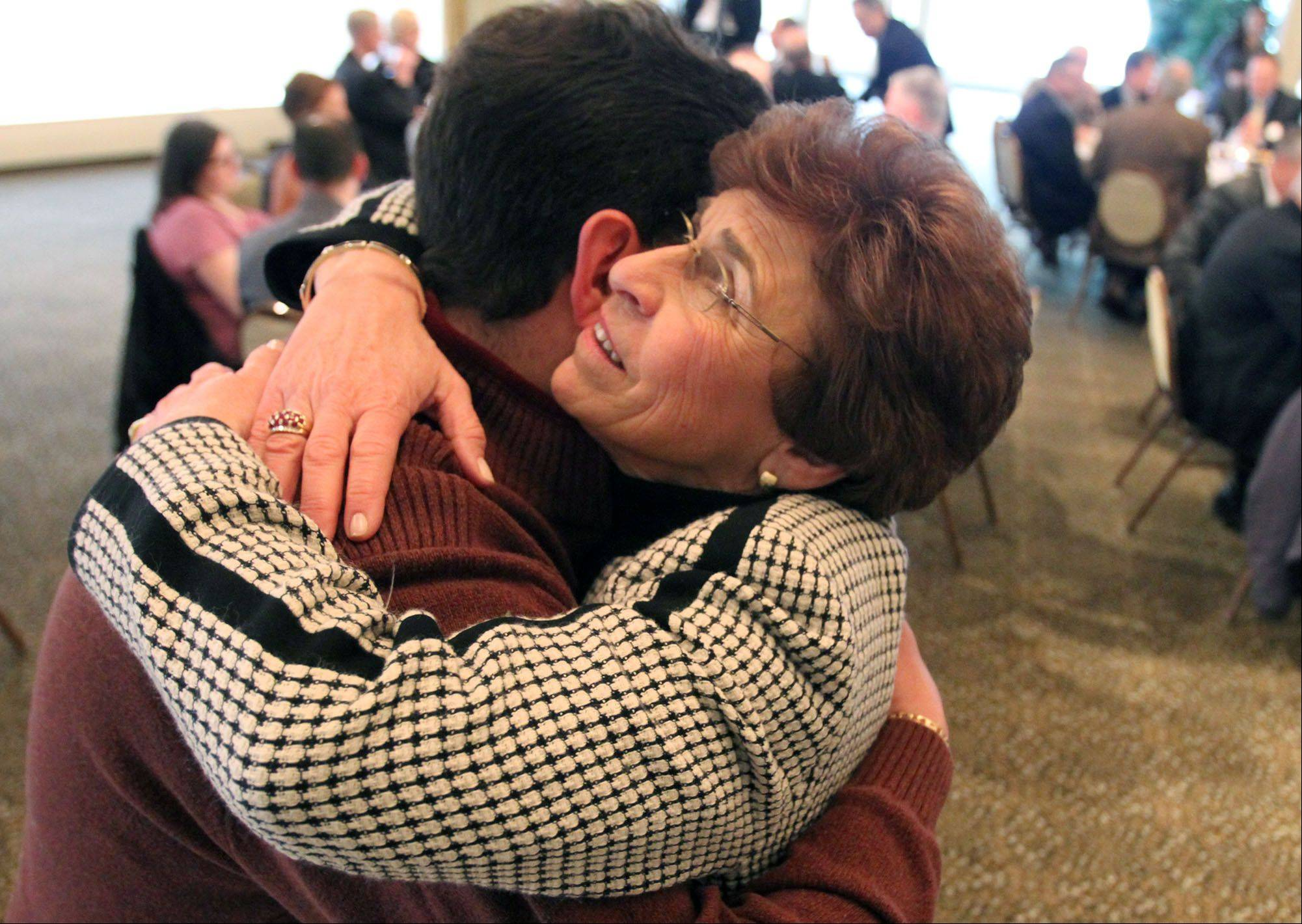 Arlene Mulder gets a hug from Trustee John Scaletta before giving her last State of the Village speech to the Arlington Heights Rotary at the Rolling Green Country Club on April 11, 2013.