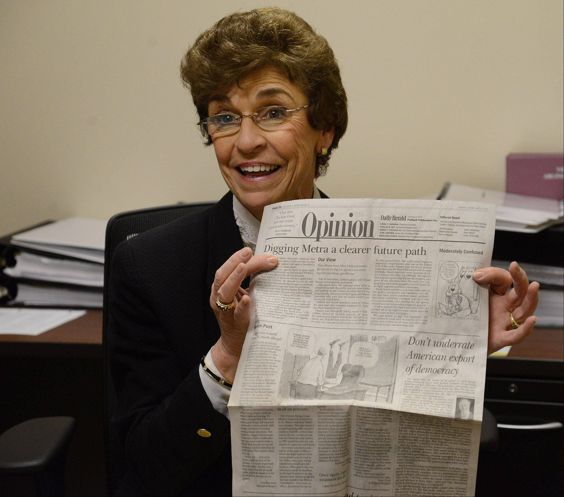 Outgoing Arlington Heights Mayor Arlene Mulder holds up a Daily Herald Opinion about Metra that she saved.