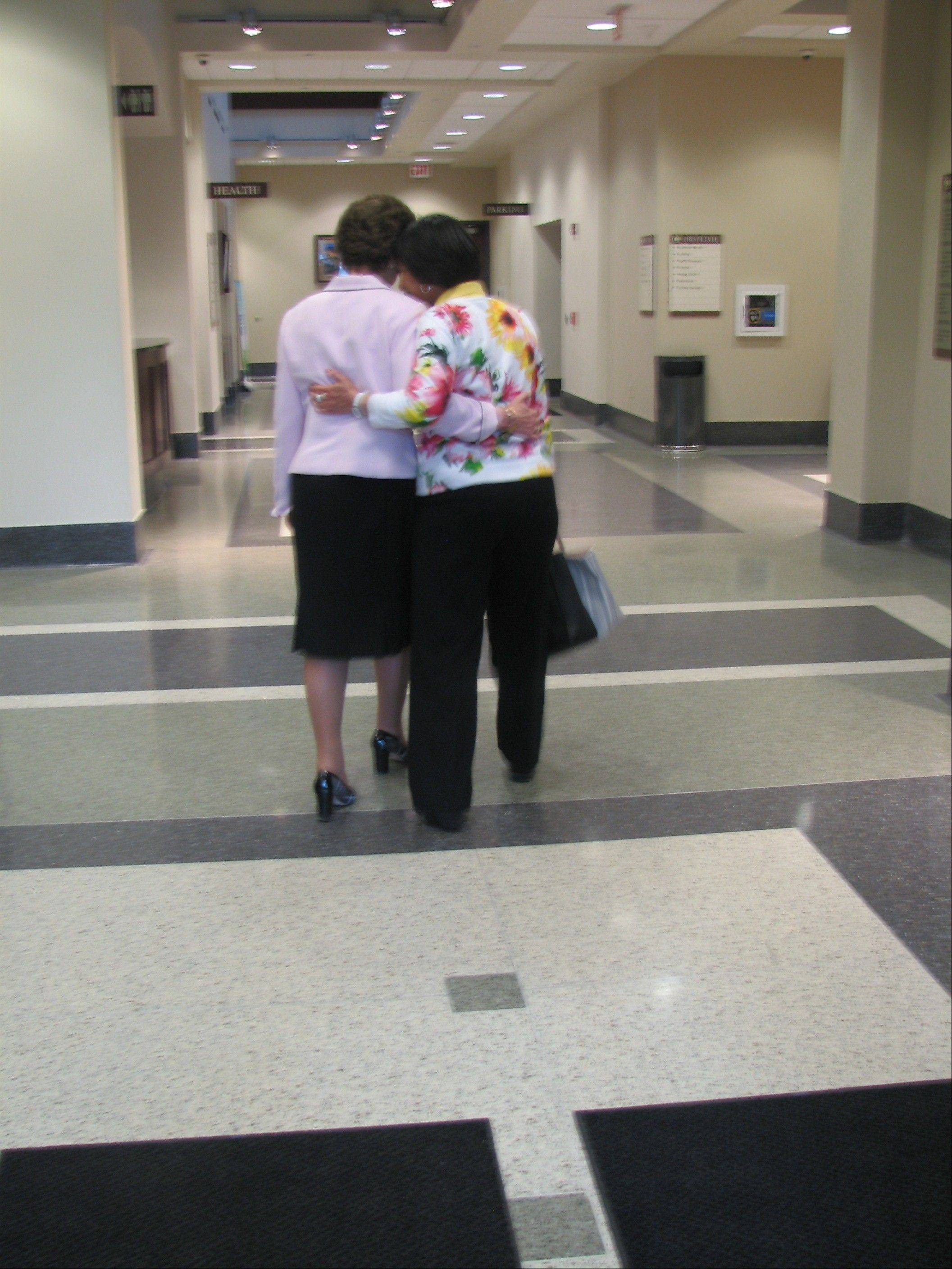 Long-time Village President Arlene Mulder, left, and long-time staffer Valerie Gerstein, walk slowly down a Village Hall hallway May 2, saying goodbye.