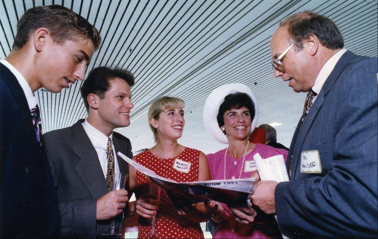 In 1993 at the track: Al Mulder goes over a racing program with, from left: his son, Michael; Vladimir Sceririn, the fiance of his daughter, Michelle; Michelle Mulder; and his wife, Village President Arlene.