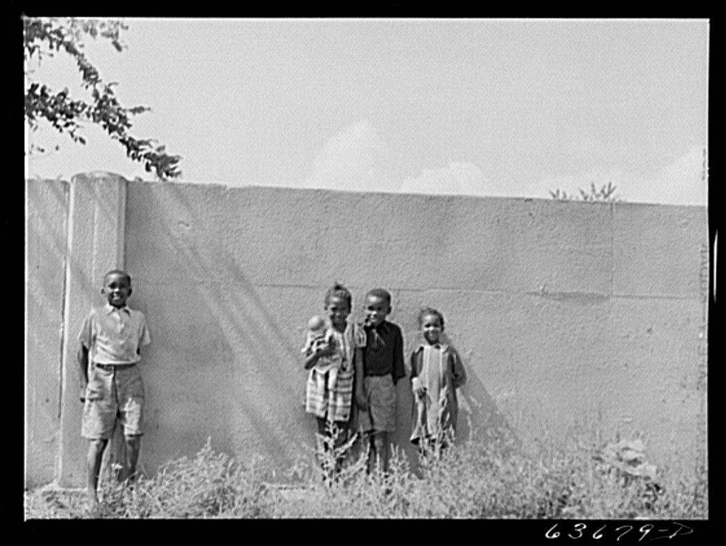 In this 1941 photo, children are shown standing in front of half-mile concrete wall in Detroit that separated homes planned for middle-class whites from blacks.