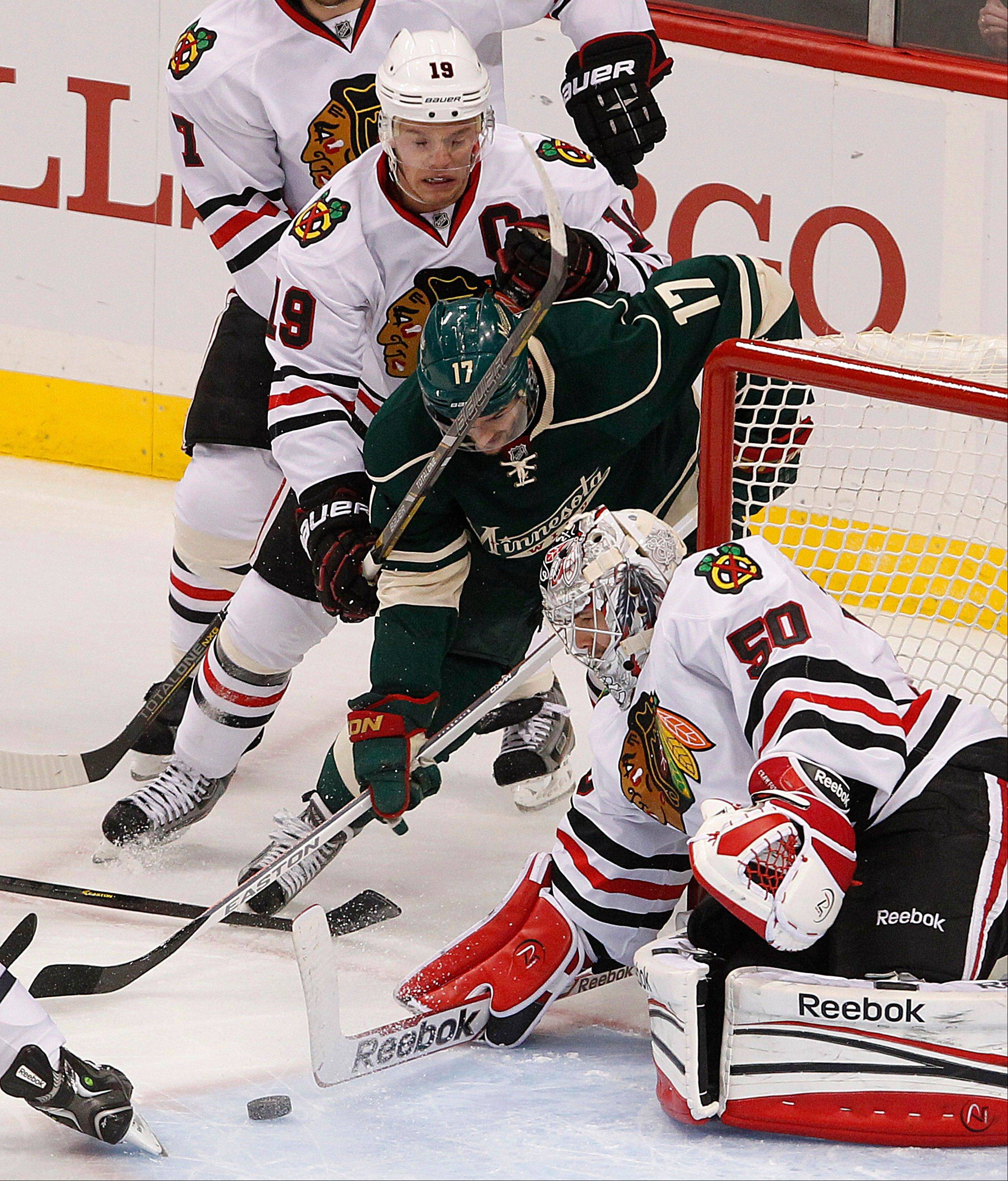 Blackhawks goalie Corey Crawford blocks a shot by the Minnesota Wild's Torrey Mitchell in the first period of Game 3 of a first-round NHL hockey Stanley Cup playoff series on Sunday, May 5, 2013, in St. Paul, Minn.