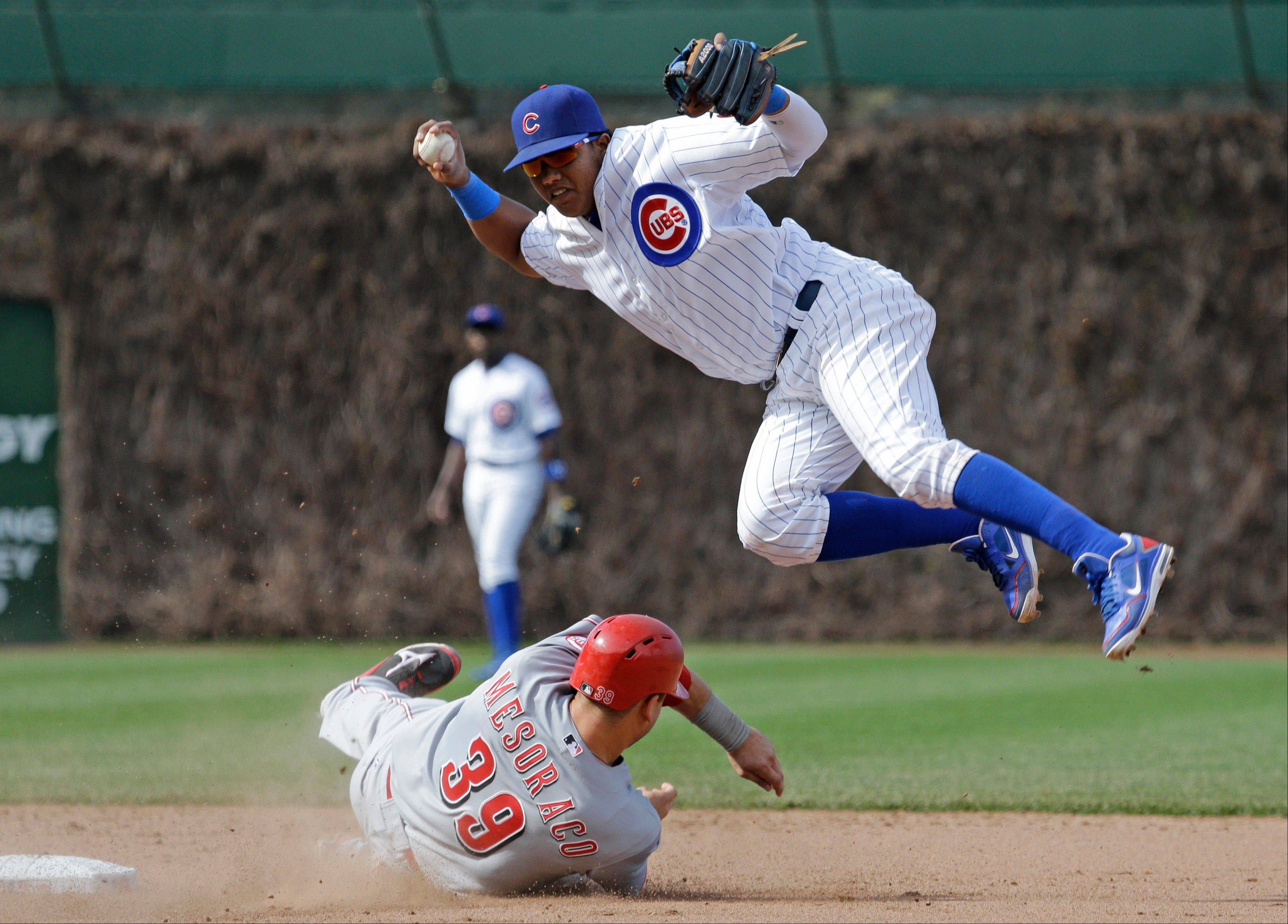 Cubs shortstop Starlin Castro, top, jumps after forcing out Cincinnati Reds' Devin Mesoraco during the eighth inning of an MLB National League baseball game in Chicago, Sunday, May 5, 2013. Cincinnati Reds' Donald Lutz was safe at first.
