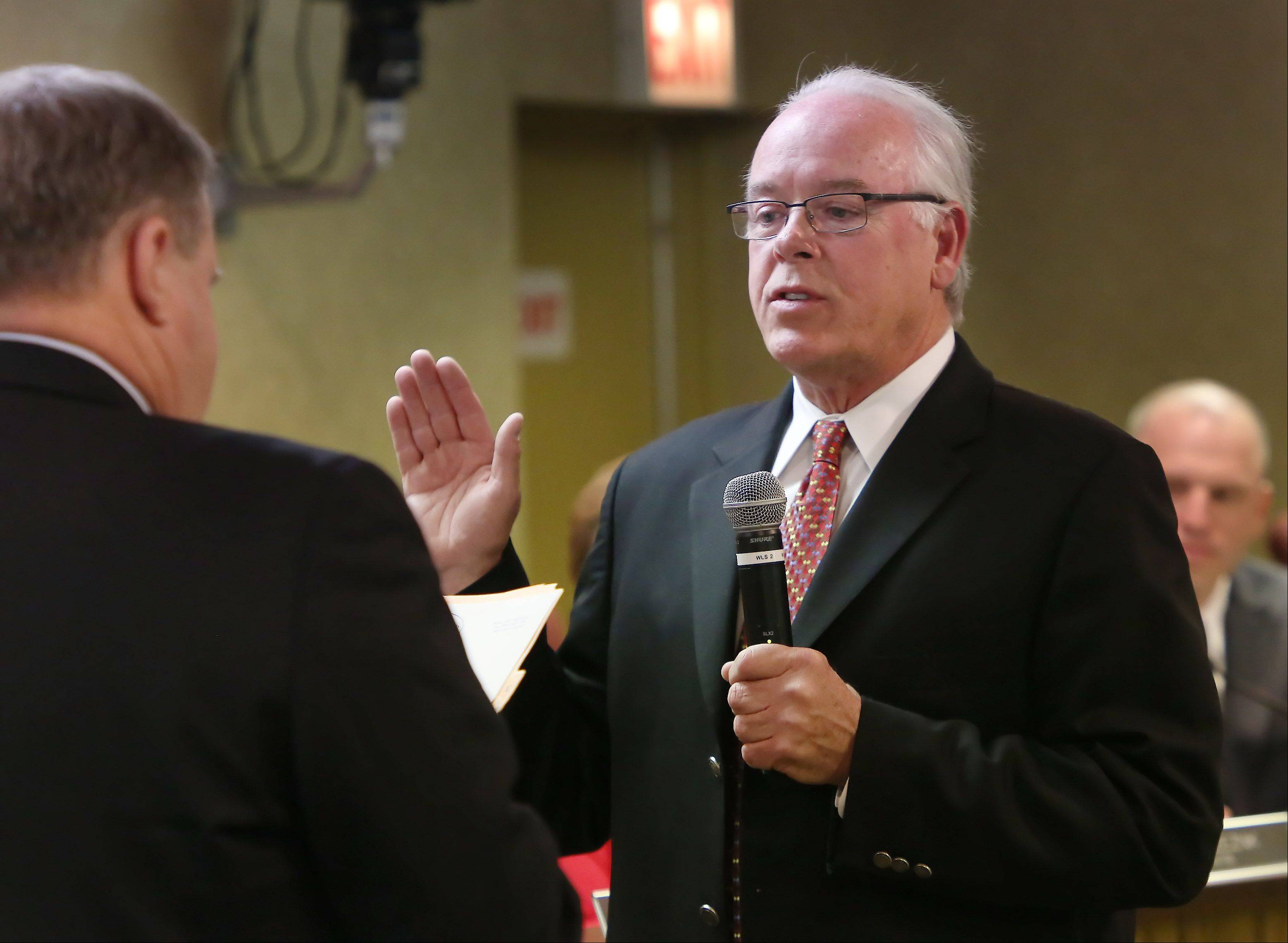 Thomas Poynton is sworn in as new Lake Zurich mayor during Monday�s village board meeting.