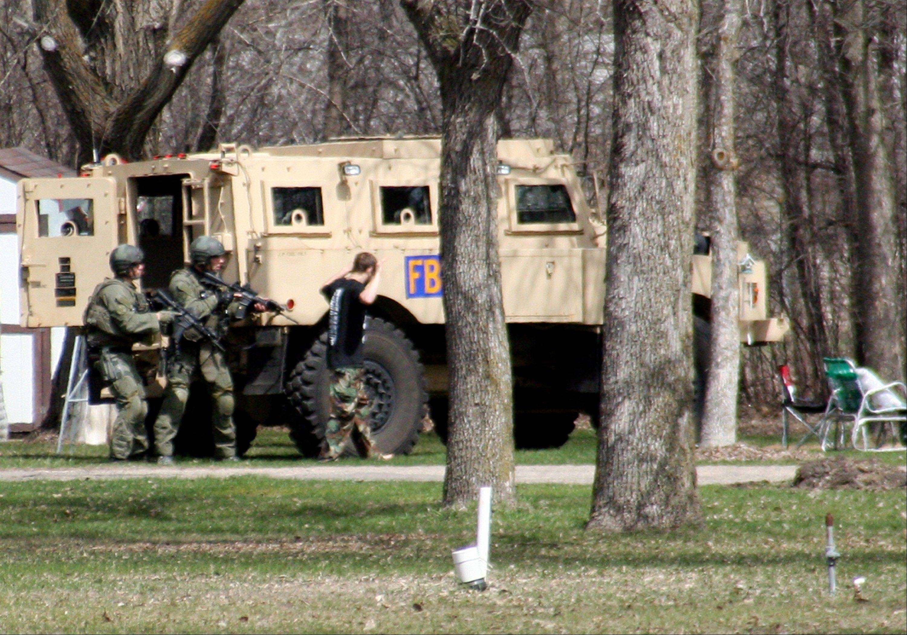 This May 3 photo shows authorities with Buford Rogers, right, during a raid on a mobile home in Montevideo, Minn. Authorities said Monday that Rogers was arrested, charged with one count of being a felon in possession of a firearm, and that the agency believes is disrupted a potential terror attack after a search of the home turned up Molotov cocktails, suspected pipe bombs and firearms.