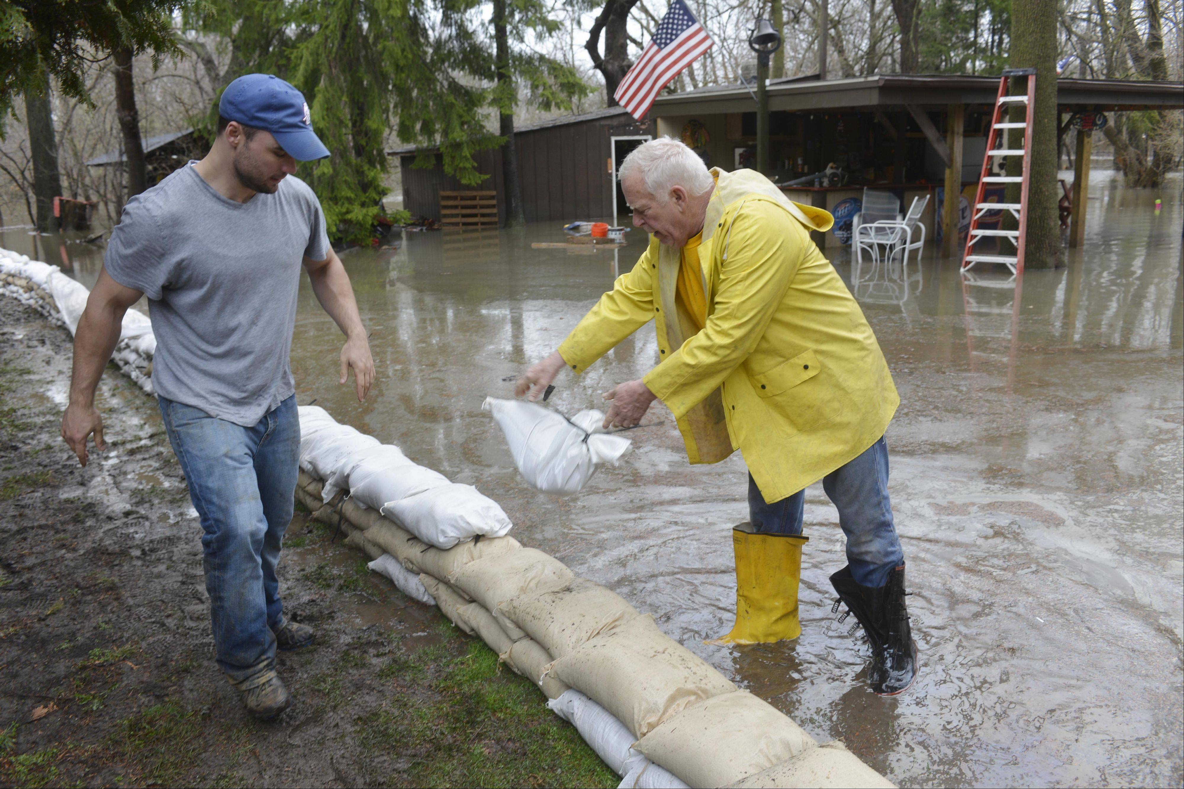 Matthew Jentel, left, and Dave Geist help build a sandbag wall around the home of James Eck last month in the flooded Big Bend neighborhood in Des Plaines.