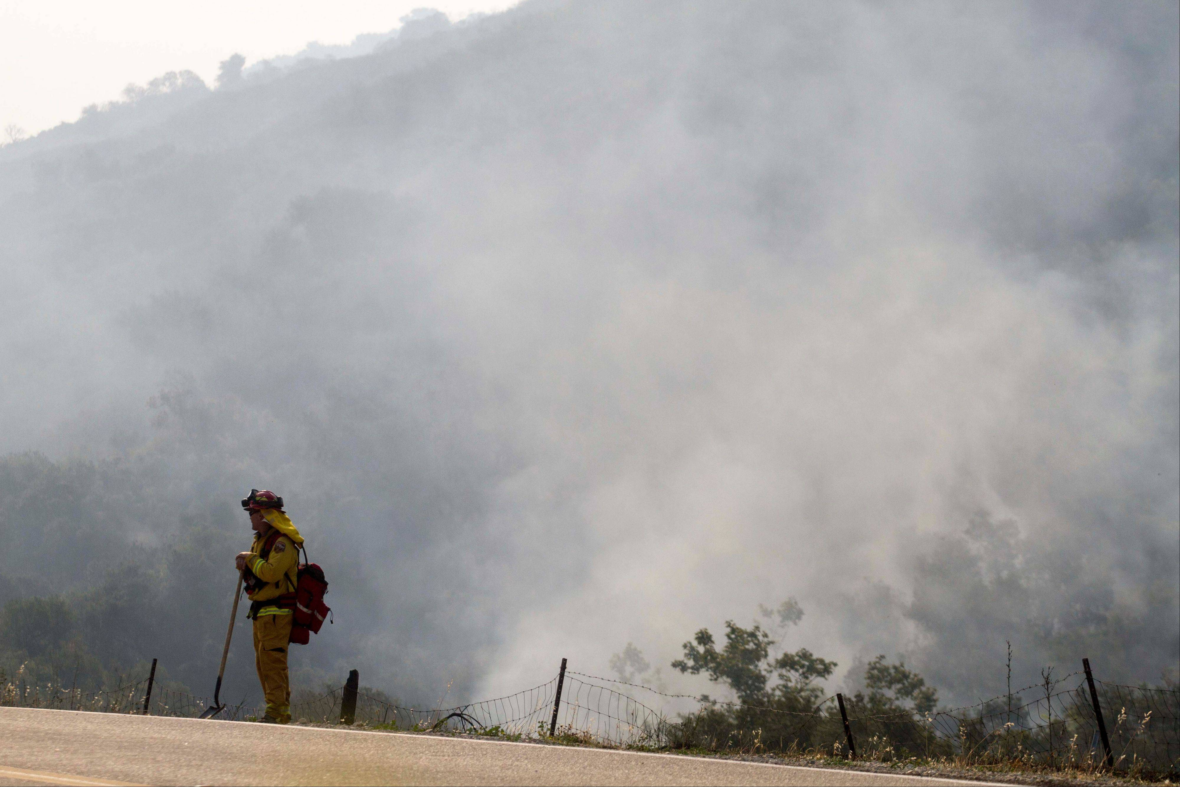 A firefighter stands watch as the smoke rises from the burnt area in Hidden Valley, Calif., Saturday. High winds and withering hot, dry air was replaced by the normal flow of damp air off the Pacific, significantly reducing fire activity.