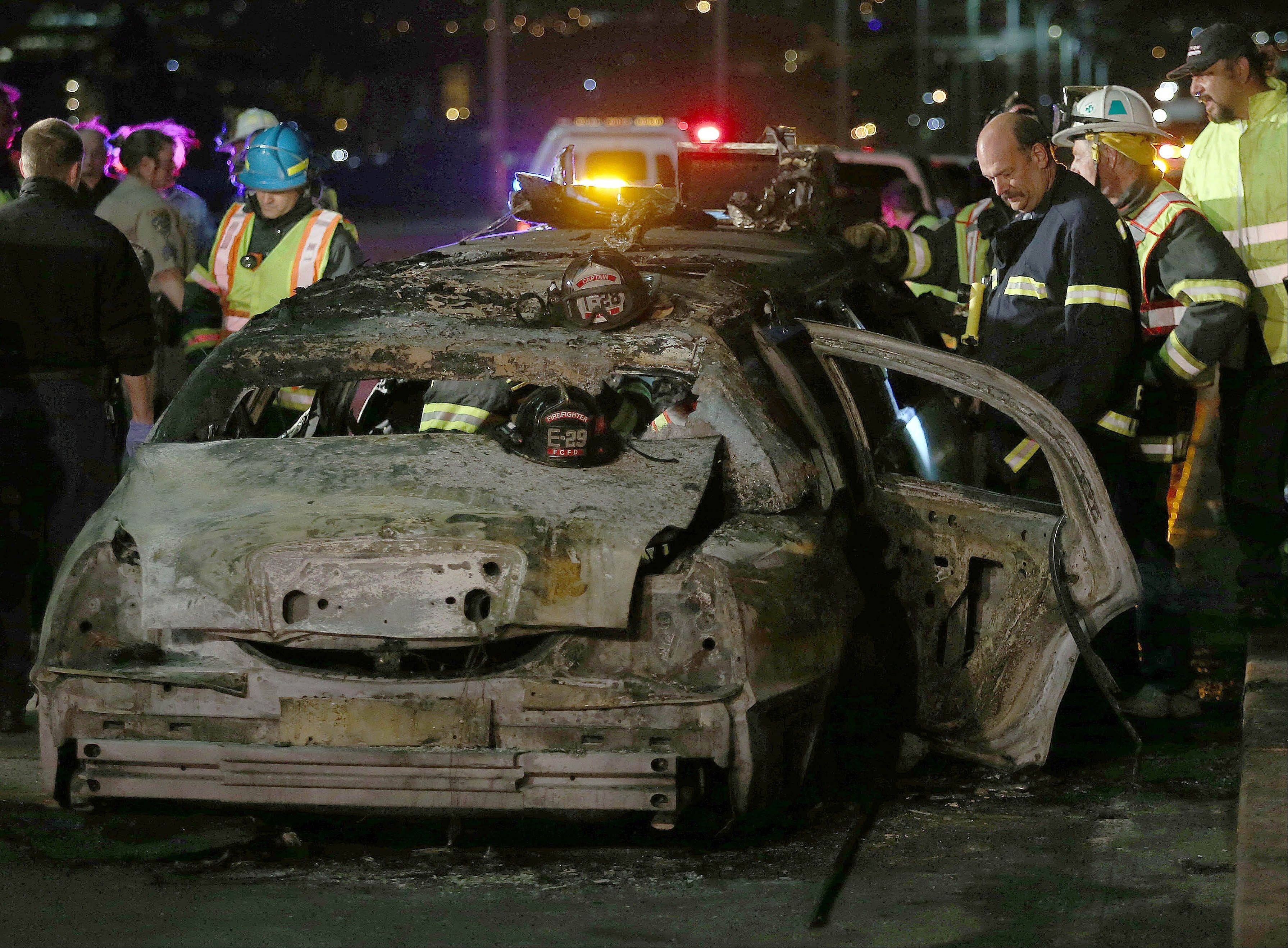 San Mateo County firefighters and California Highway Patrol personnel investigate the scene of a limousine fire on the westbound side of the San Mateo-Hayward Bridge in Foster City, Calif., on Saturday night. Five people died when they were trapped in the limo that caught fire as they were traveling, and four others and the driver were able to escape, according to the Oakland Tribune-Bay Area News Group.