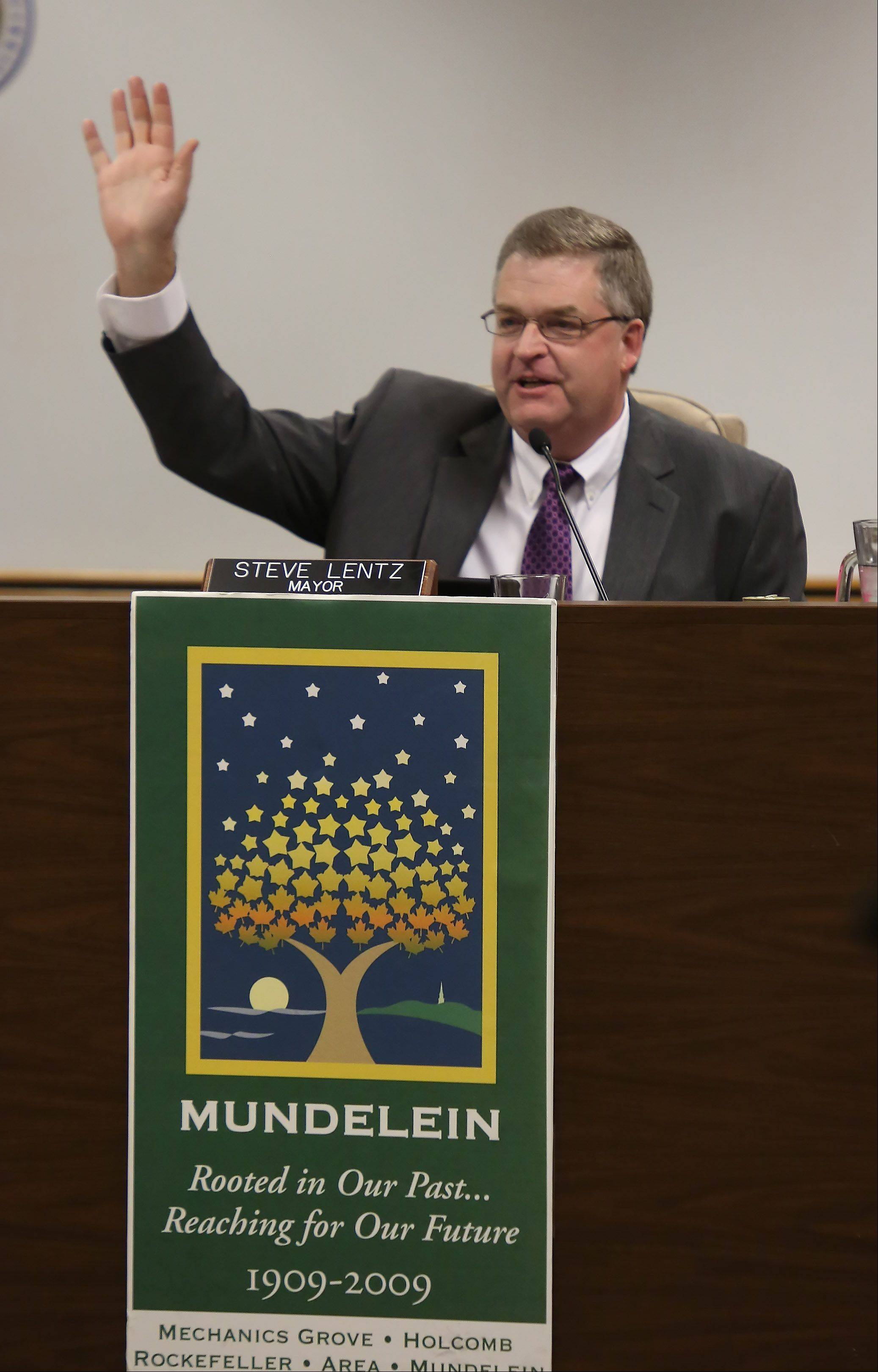 Steve Lentz waves to family and friends after he was sworn in as the new Mundelein mayor during the village board meeting Monday at the Mundelein Fire Station.