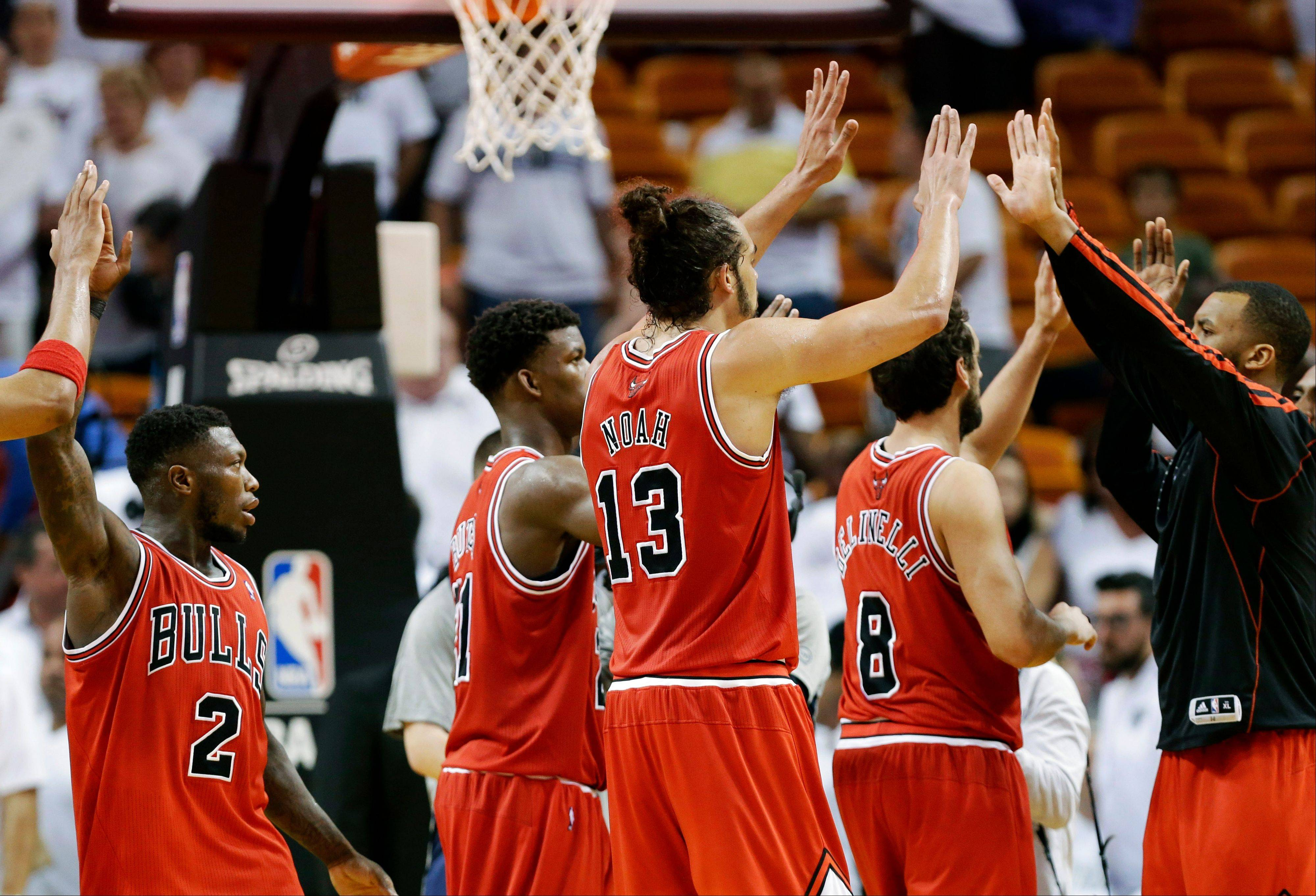 Chicago Bulls' Nate Robinson (2) and Joakim Noah (13) celebrate with their teammates after defeating the Miami Heat 93-86 in Game 1 of their NBA basketball playoff series in the Eastern Conference semifinals, Monday, May 6, 2013, in Miami.