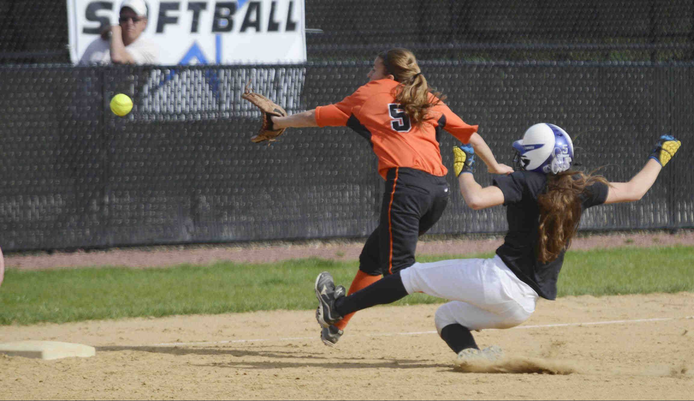 St. Charles North�s Sabrina Rabin steals third base after stealing second in the first inning as St. Charles East�s Alexis Perez reaches for the throw. Rabin stole four bases in the North Stars� 10-0 victory.