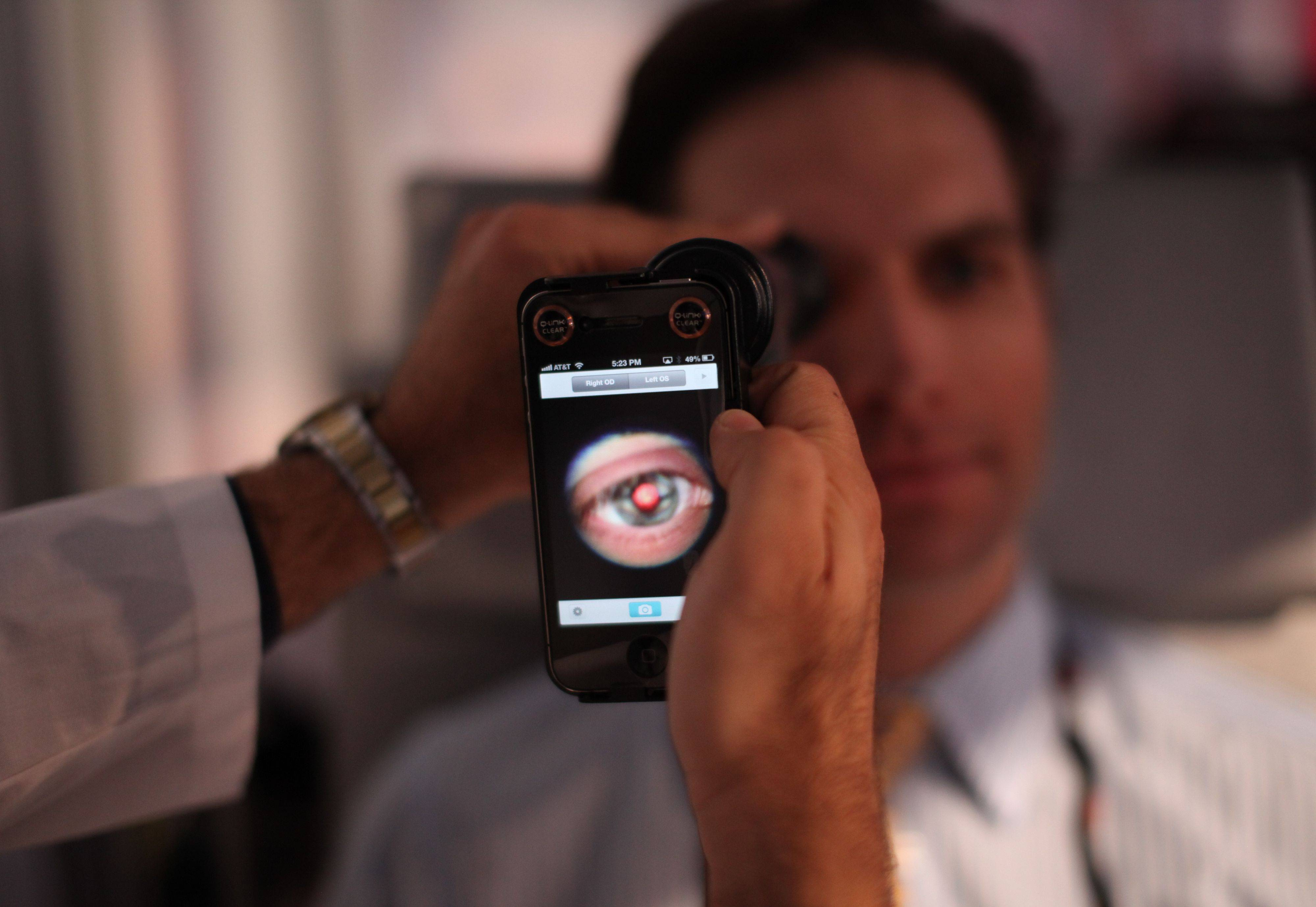 A medical student prepares to photograph the inside of someone's eye using a special tool that taps a smartphone's camera. Companies are developing miniature medical tools that hook onto smartphones to provide almost a complete physical.