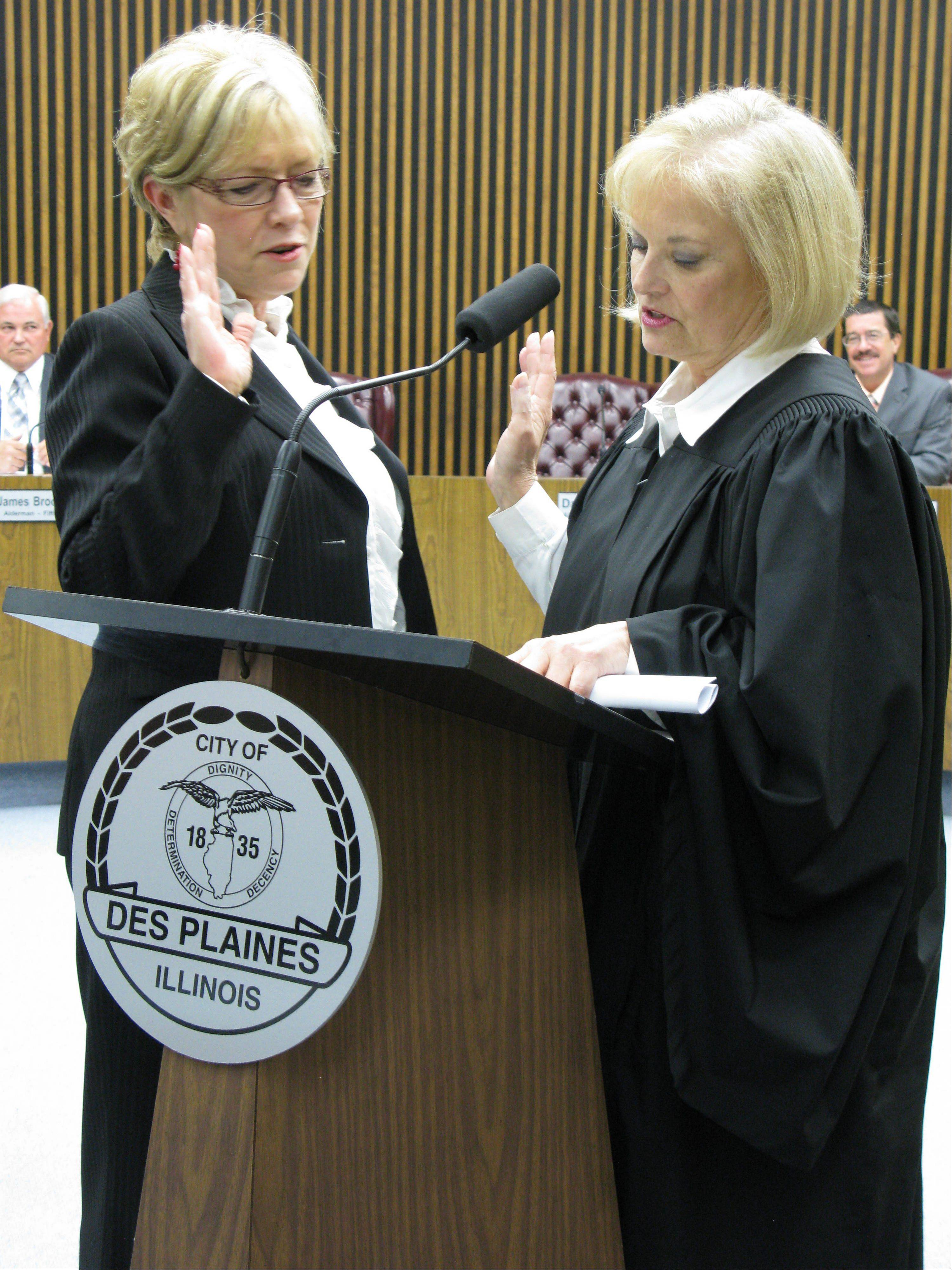 Appellate Court Judge Aurelia Pucinski, right, administers the oath of office to Des Plaines 1st Ward Alderwoman Patti Haugeberg Monday night.