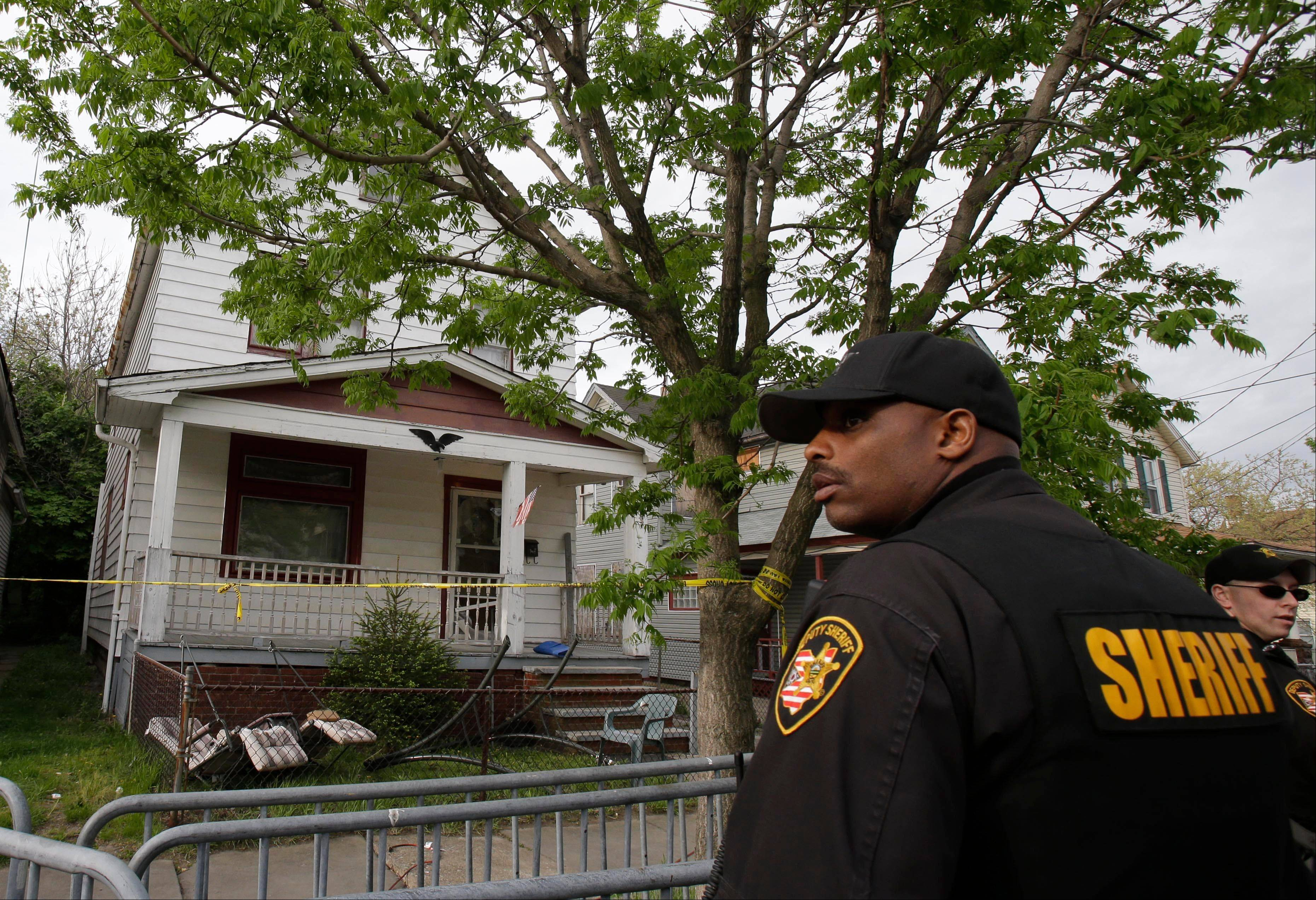 A sheriff's deputy stands outside a house where three women escaped Tuesday, May 7, 2013, in Cleveland. Three women who went missing separately about a decade ago were found in the home Monday just south of downtown and likely had been tied up during years of captivity, said police, who arrested three brothers.