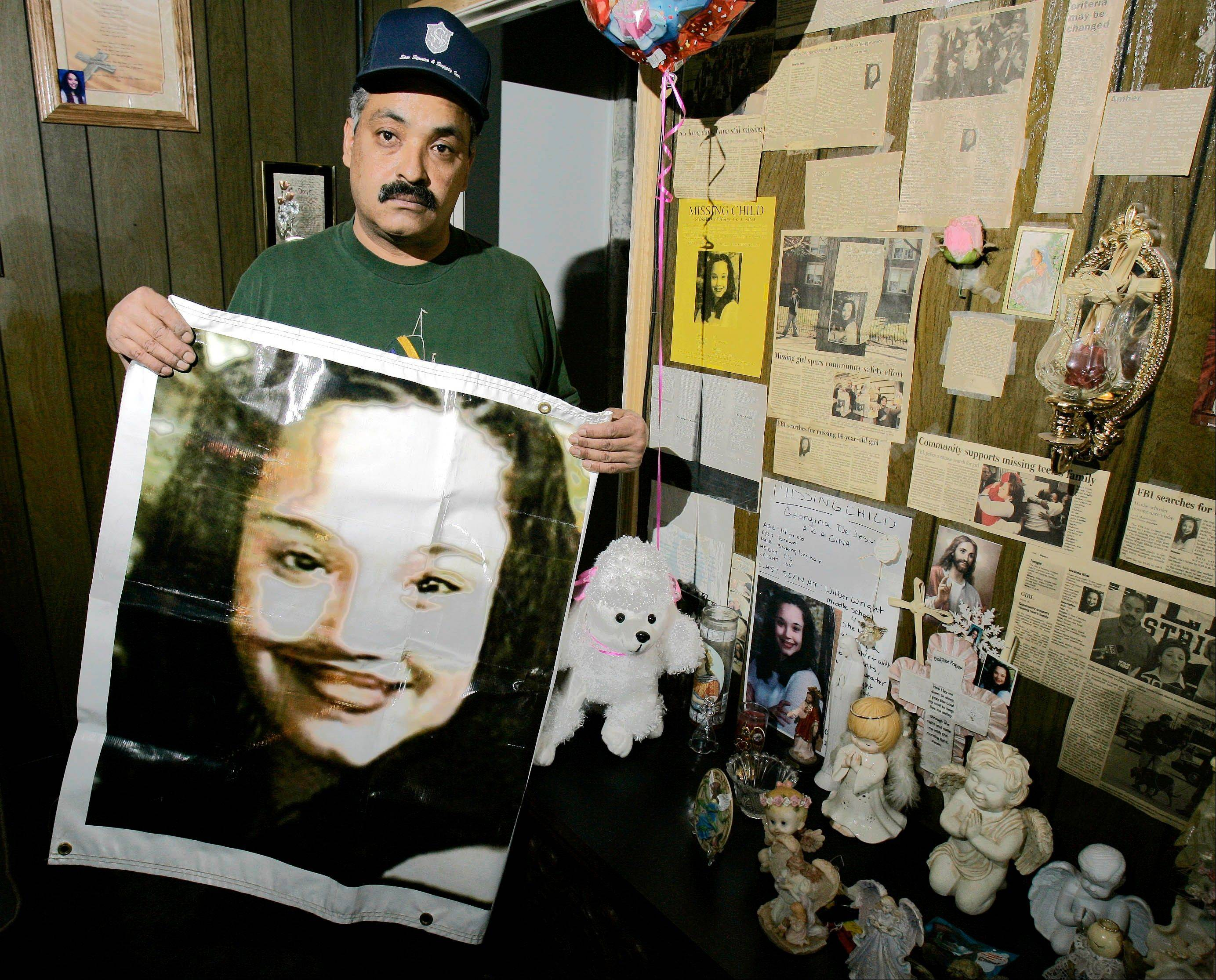 This Friday, March 3, 2004, file photo shows Felix DeJesus holding a banner showing his daughter's photograph and standing by a memorial in his living room in Cleveland. Cleveland police say Gina DeJesus and Amanda Berry, who went missing as teenagers about a decade ago, have been found alive in a residential area about two miles south of downtown.