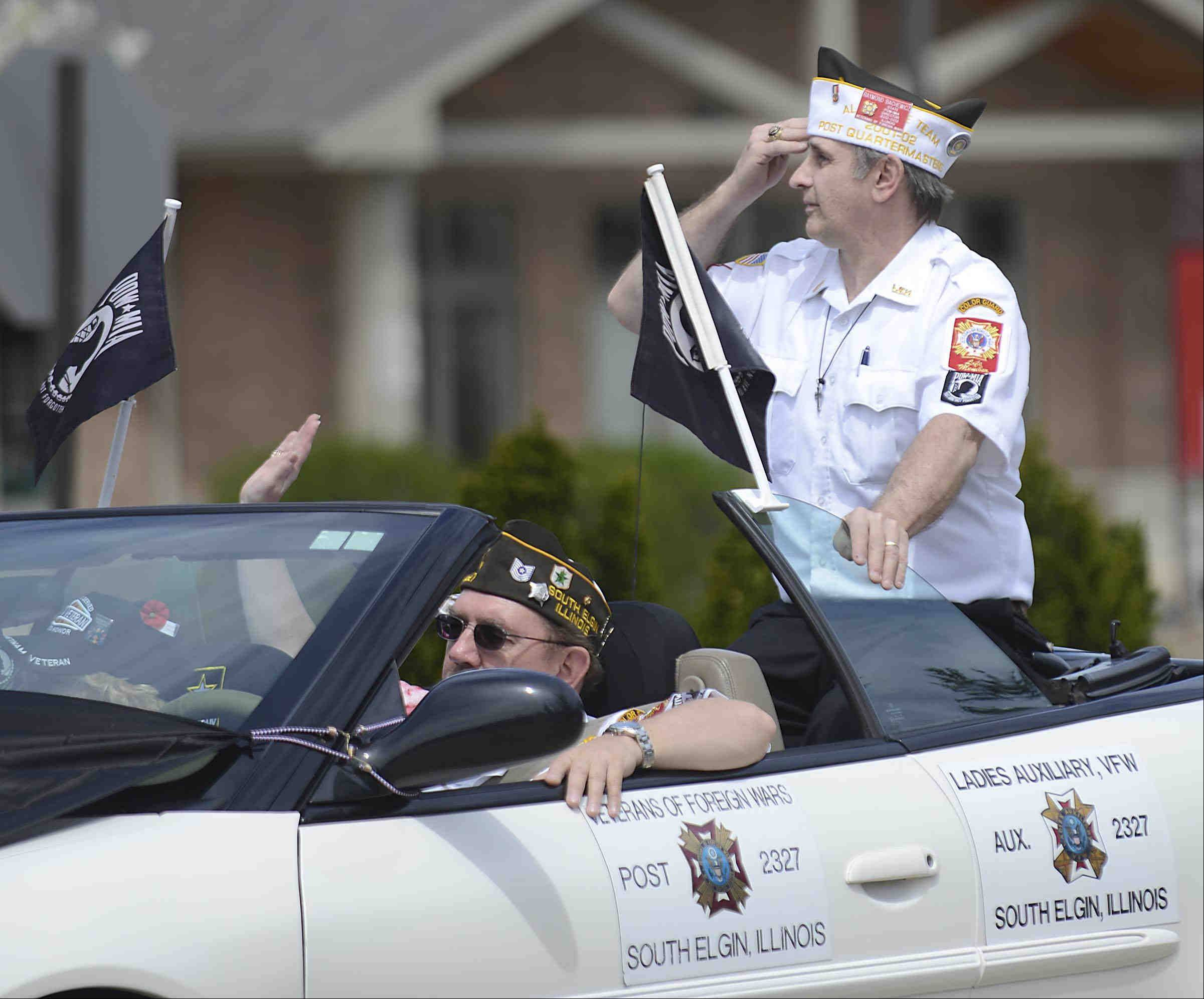 Ray Bachewicz, of South Elgin, director of the POW/MIA program for the VFW of Illinois, salutes the announcer's stand as he passes by Sunday during the parade.