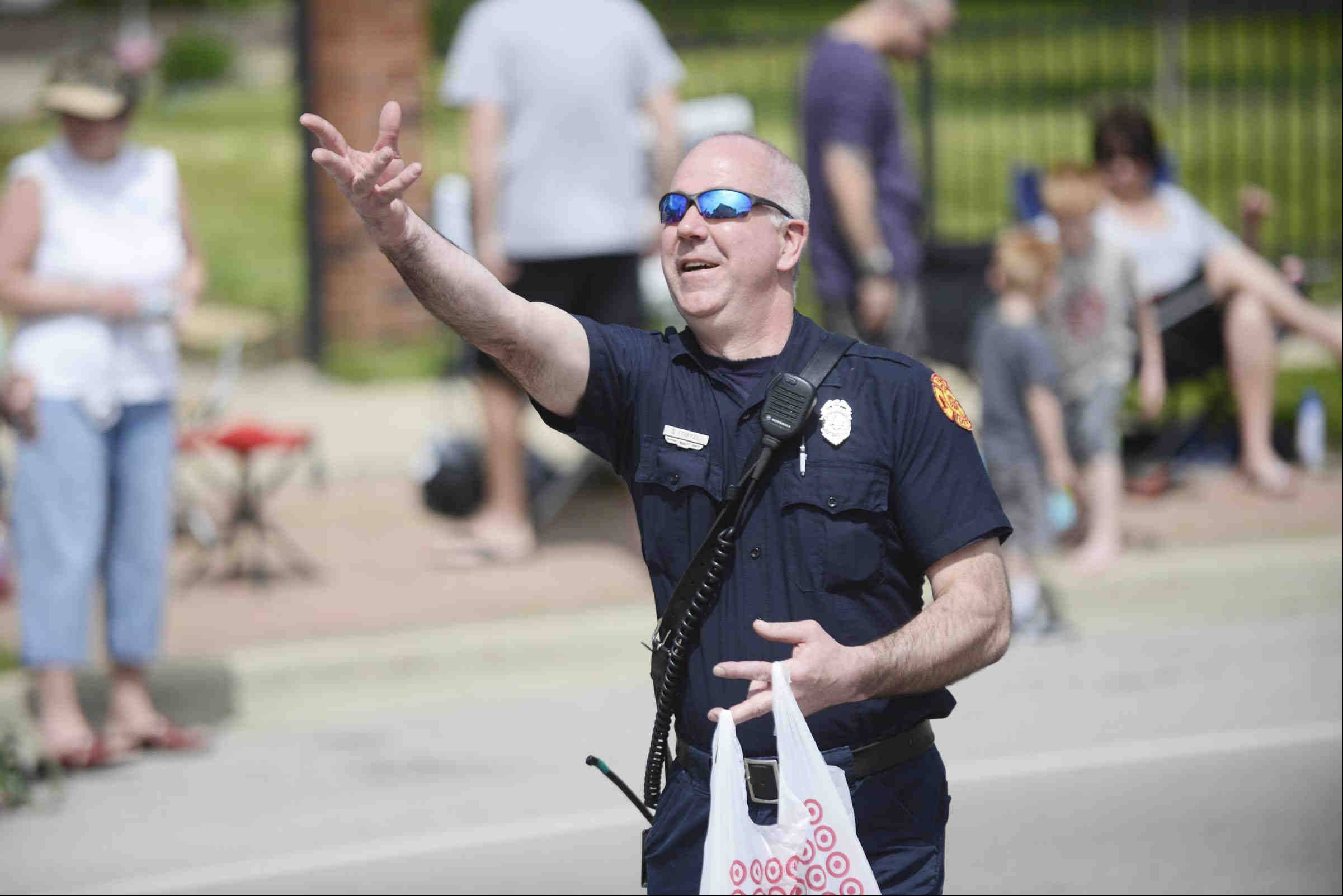 "Batavia Firefighter/EMT Greg Stoffel tosses candy to the crowd Sunday during the Batavia Loyalty Day Parade on Wilson Street. ""The VFW Tree of Life"" was the theme."