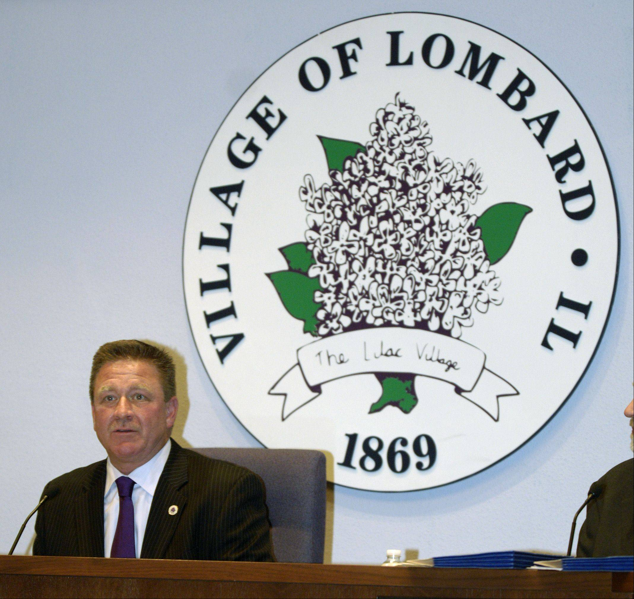 Lombard Village President Keith Giagnorio takes his seat in front of the village's lilac logo, where he will sit as he runs board meetings for the next four years.
