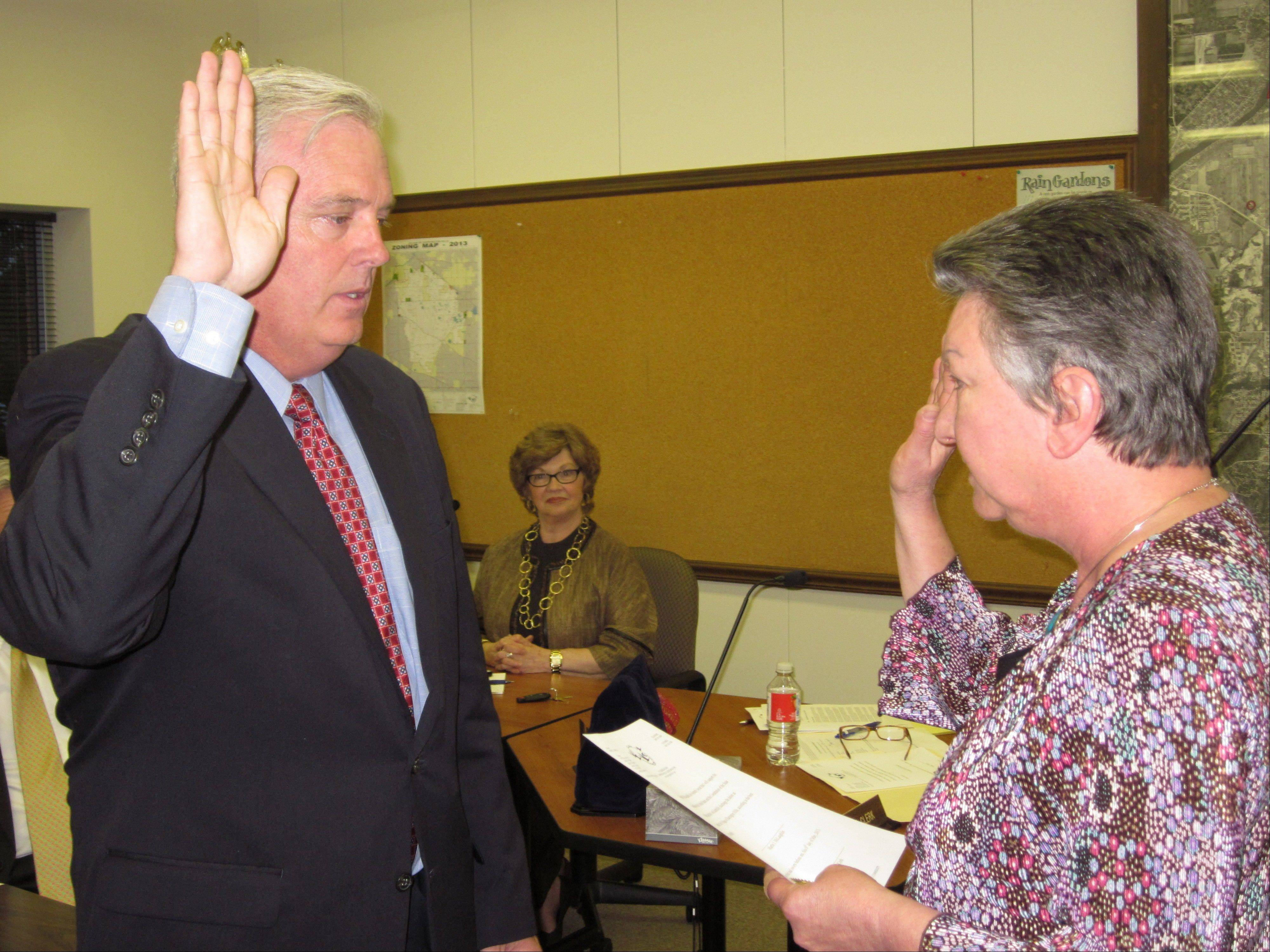 Newly elected Barrington Hills Village President Martin McLaughlin takes the oath of office Monday, administered by Village Clerk Dolores Trandel.