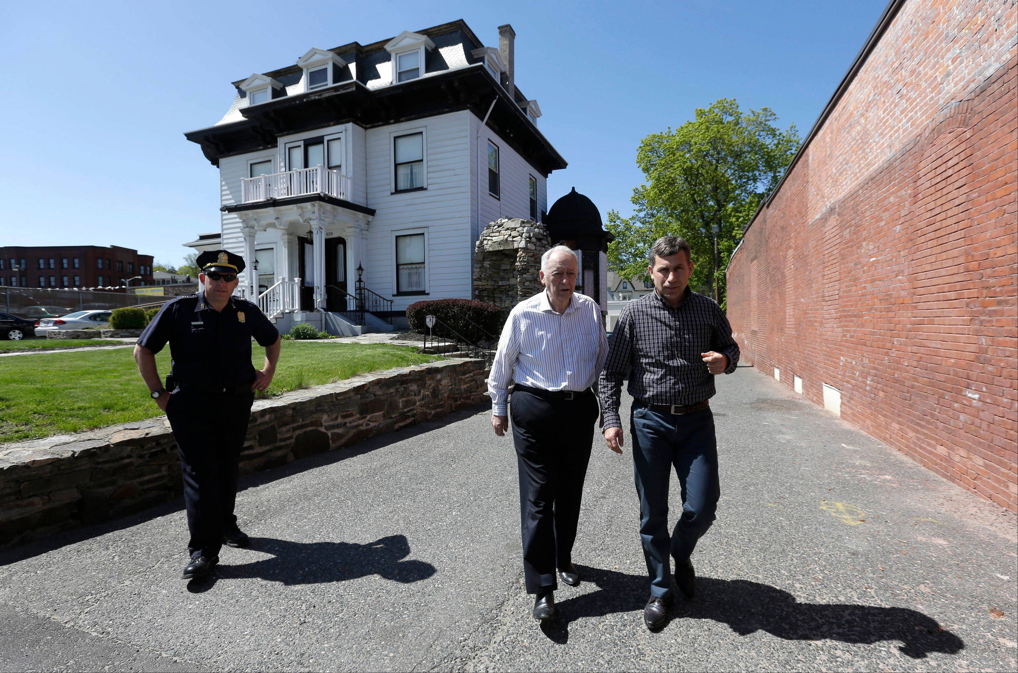 Ruslan Tsarni, right, uncle of the dead Boston Marathon bombing suspect, approaches members of the media, not shown, in front of the Graham, Putnam, and Mahoney Funeral Parlors, in Worcester, Mass., as funeral director and owner Peter Stefan, center, walks with him Sunday. Stefan has pleaded for government officials to use their influence to convince a cemetery to bury the suspect, but so far no state or federal authorities have stepped forward.