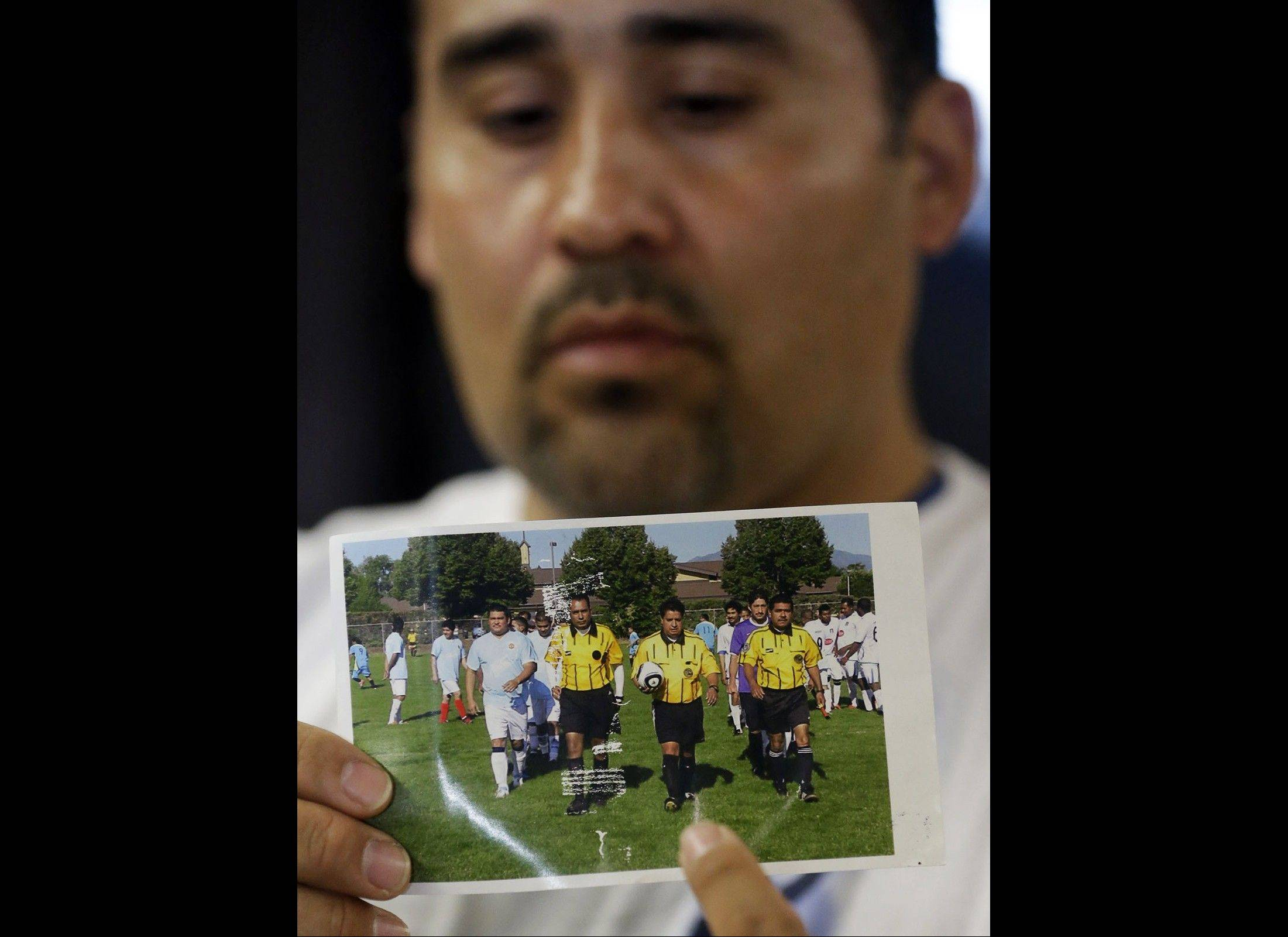 Jose Lopez points to an undated photo of Ricardo Portillo, center, his brother-in-law, following a news conference at Intermountain Medical Center in Murray, Utah. Portillo, a 46-year-old soccer referee who was punched by a teenage player during a game and later slipped into a coma, died Saturday night, police said.