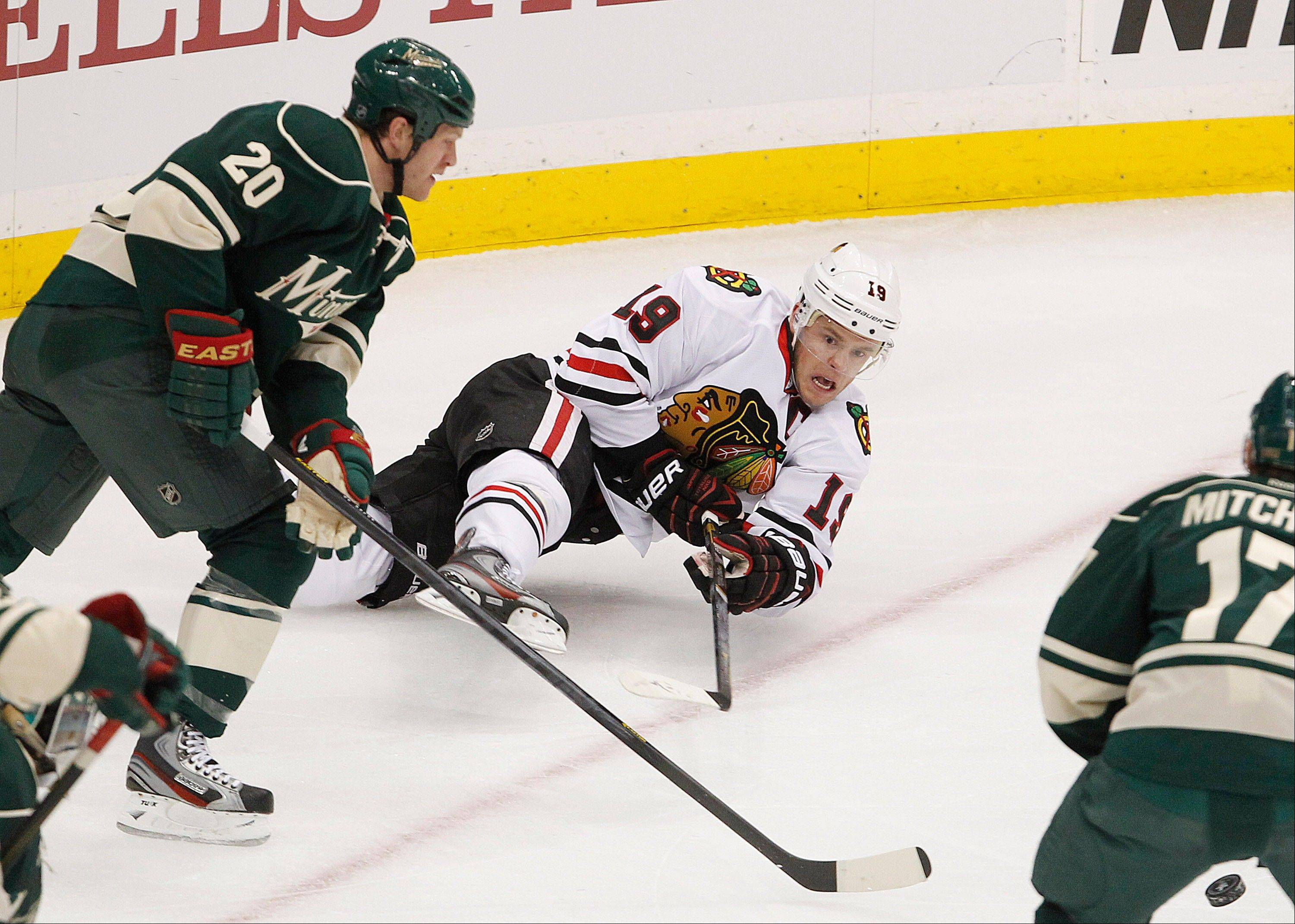 Blackhawks captain Jonathan Toews shoots as he falls in front of Minnesota defenseman Ryan Suter in Sunday's first period of Game 3 in the teams' first-round playoff series.