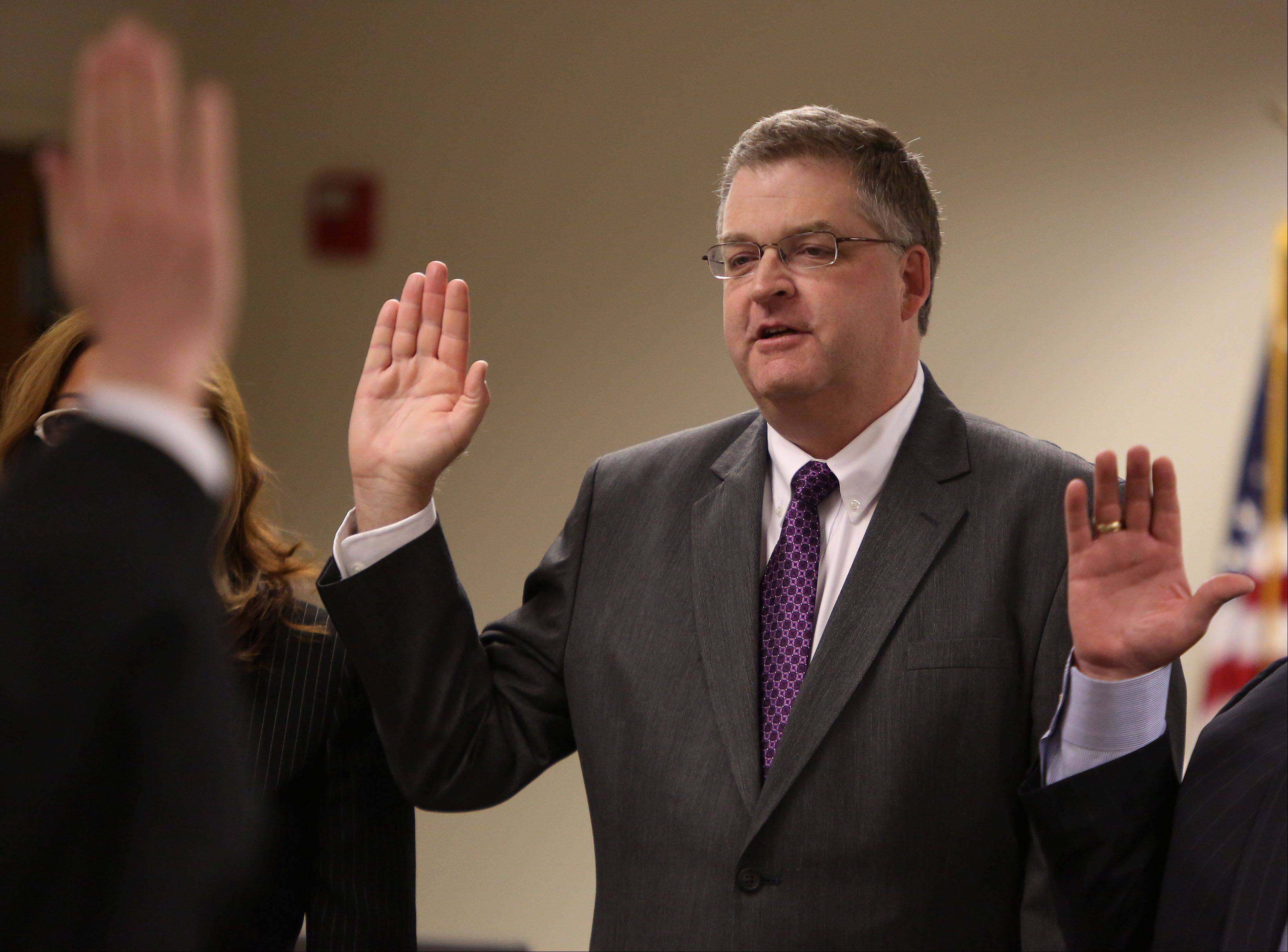 Steve Lentz takes the oath of office as the new mayor of Monday during the village board meeting Monday at the Mundelein Fire Station.