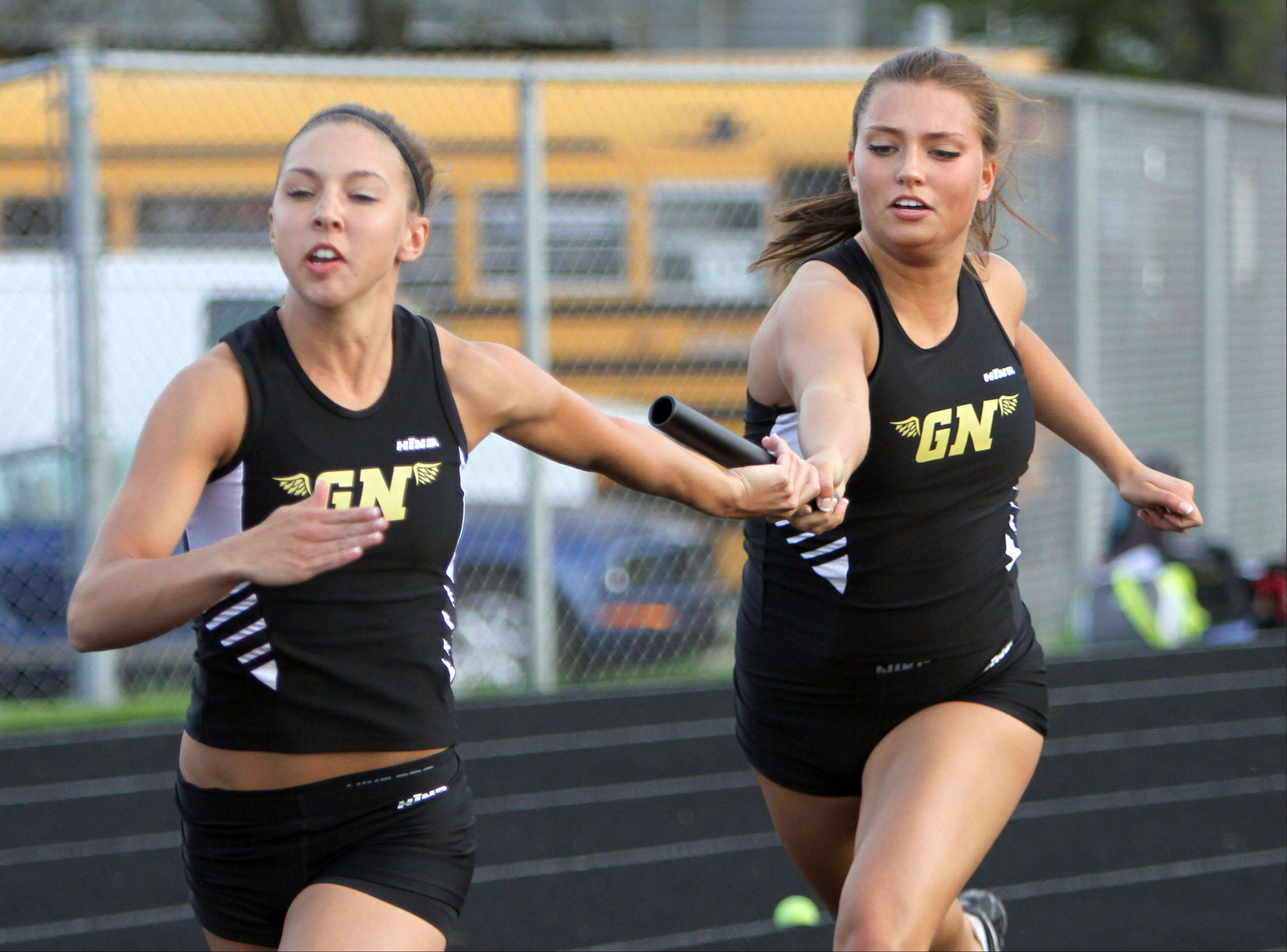 Grayslake North's Pam Bazan, right, hands off to Sarah Schmitke in the 400-meter relay during the Fox Valley Conference girls track meet Monday at Grayslake Central High School.