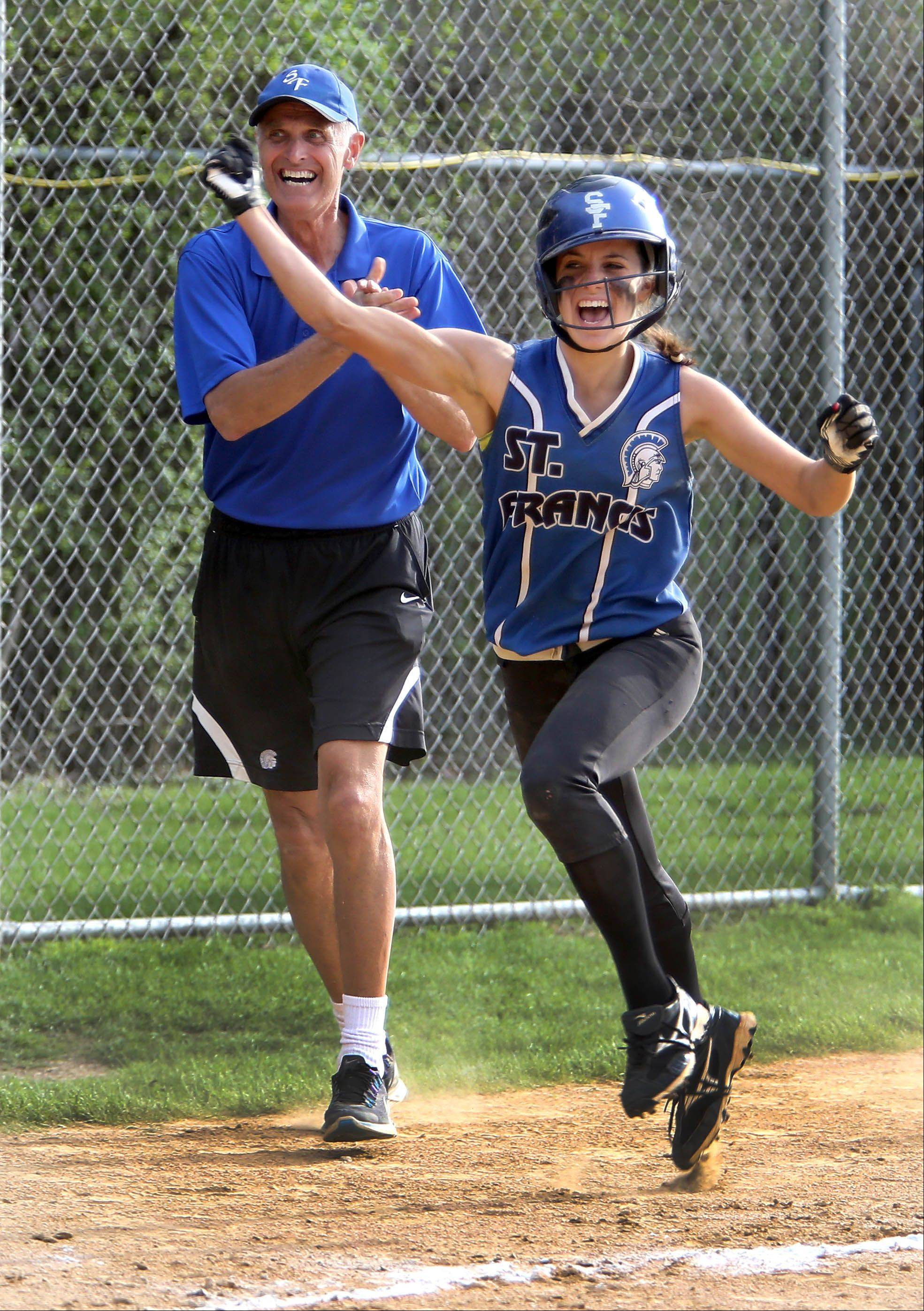 Head coach Ralph Remus is all smiles as Alyssa Fernandez comes home after hitting a game-winning two-run home run in the bottom of the 7th against Montini Catholic during girls softball on Monday in Wheaton.