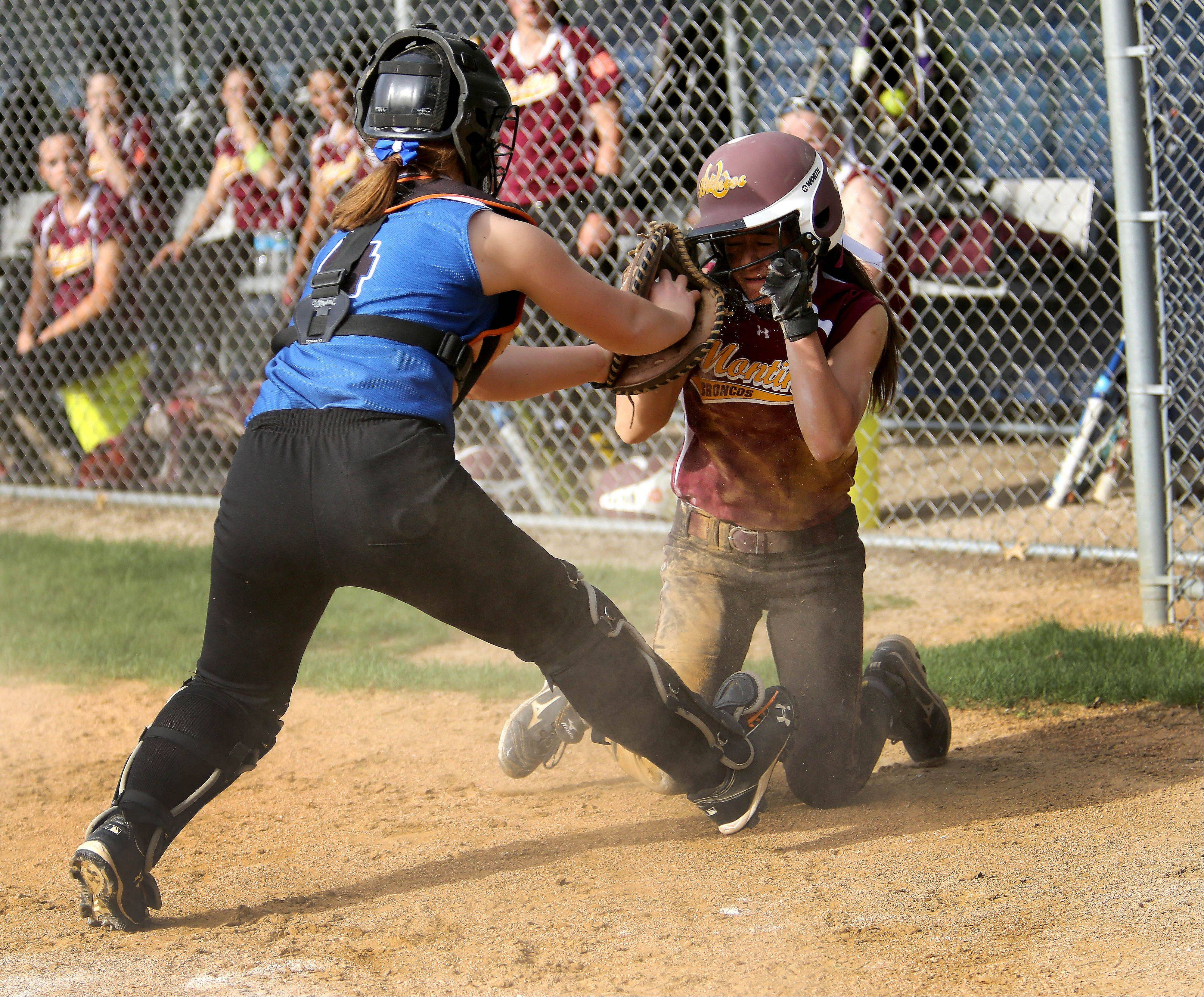 St. Francis catcher Fiona Summers tags out Isabell Alexander of Montini Catholic at home plate during girls softball on Monday in Wheaton.
