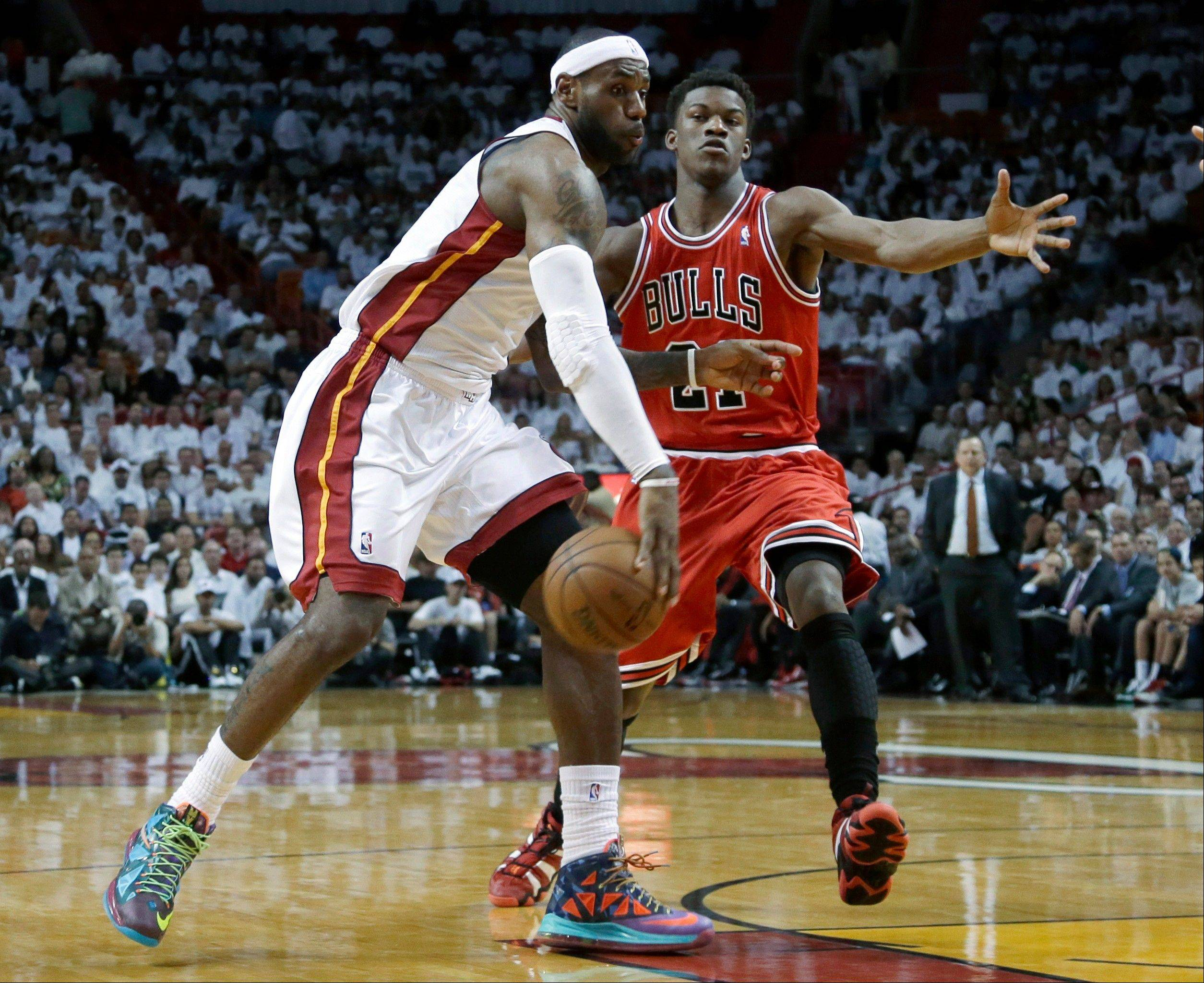 Miami Heat forward LeBron James, left, passes around Chicago Bulls forward Jimmy Butler during the first half of Game 1 of the NBA basketball playoff series in the Eastern Conference semifinals, Monday, May 6, 2013 in Miami.