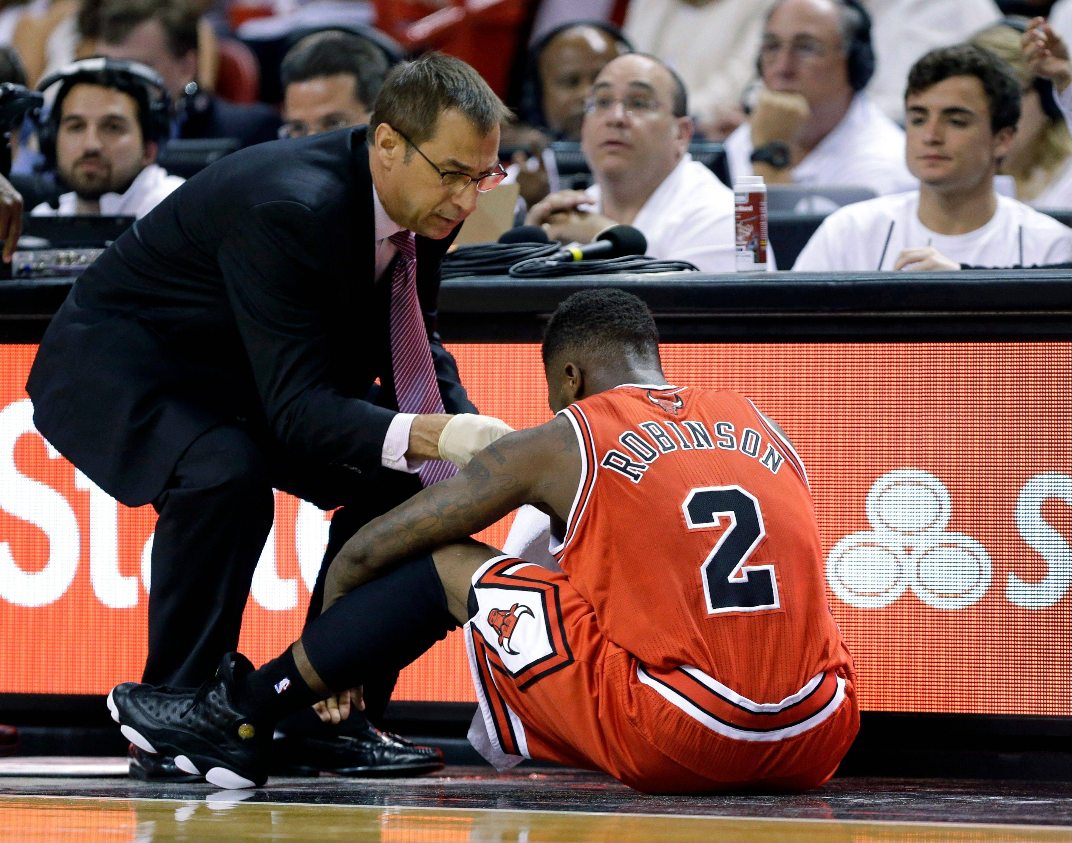 Chicago Bulls guard Nate Robinson (2) is tended to after an injury during the first half of Game 1 of the NBA basketball playoff series in the Eastern Conference semifinals against the Miami Heat, Monday, May 6, 2013 in Miami.